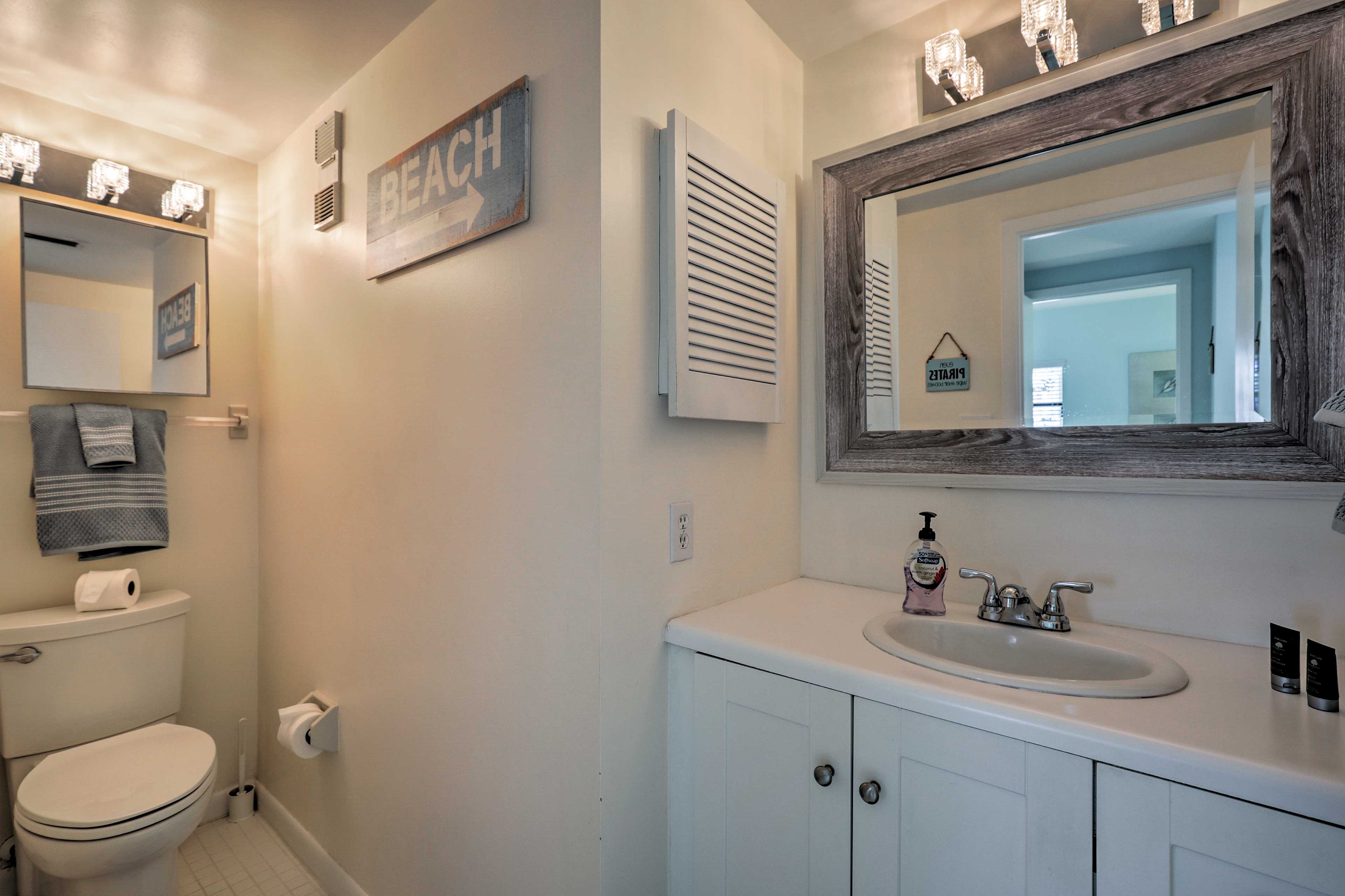 The spacious full bathroom is furnished with beach-inspired decor.