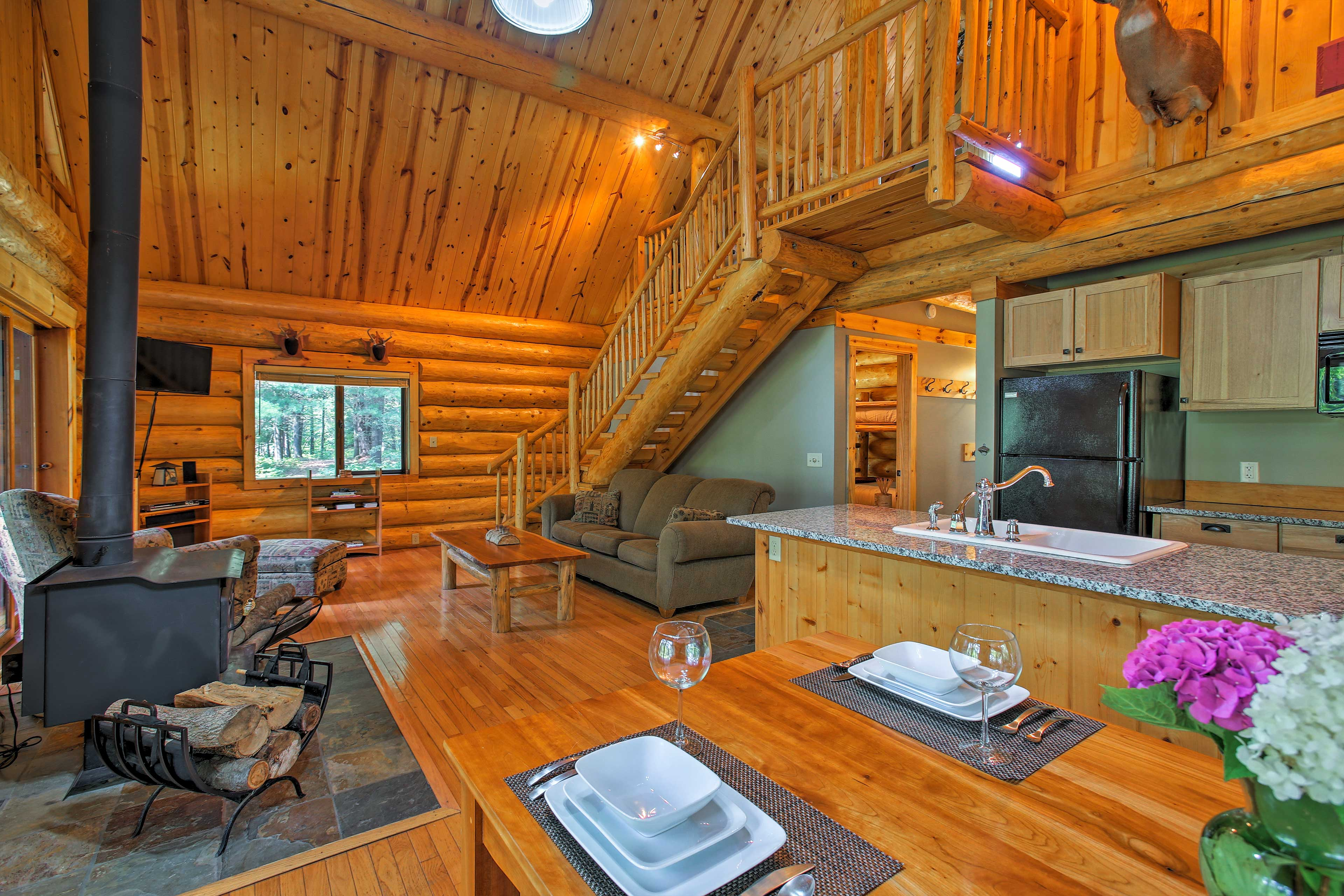 The living room features a gorgeous vaulted ceiling with an exposed log beam.