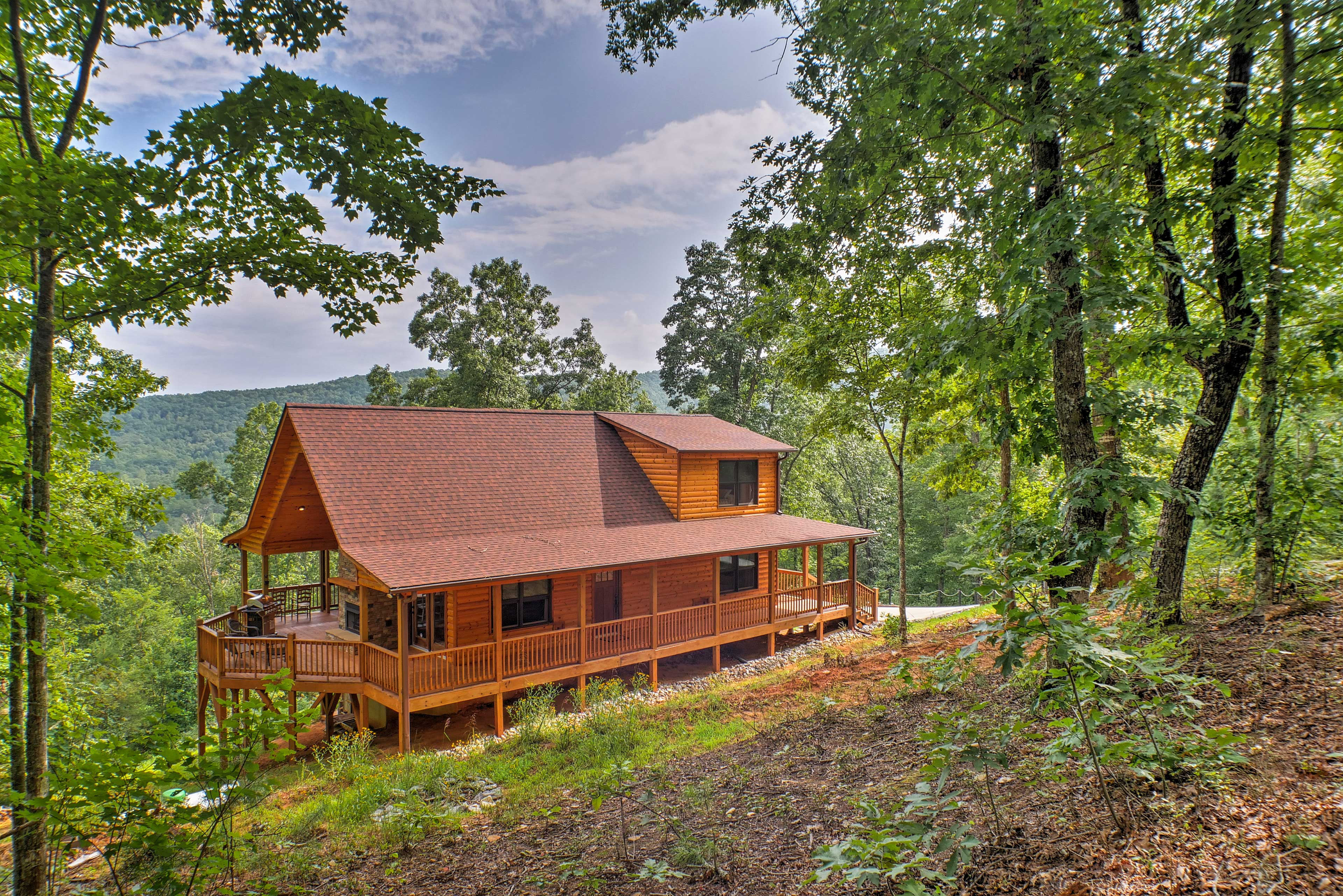 The charming home is surrounded by lush scenery.