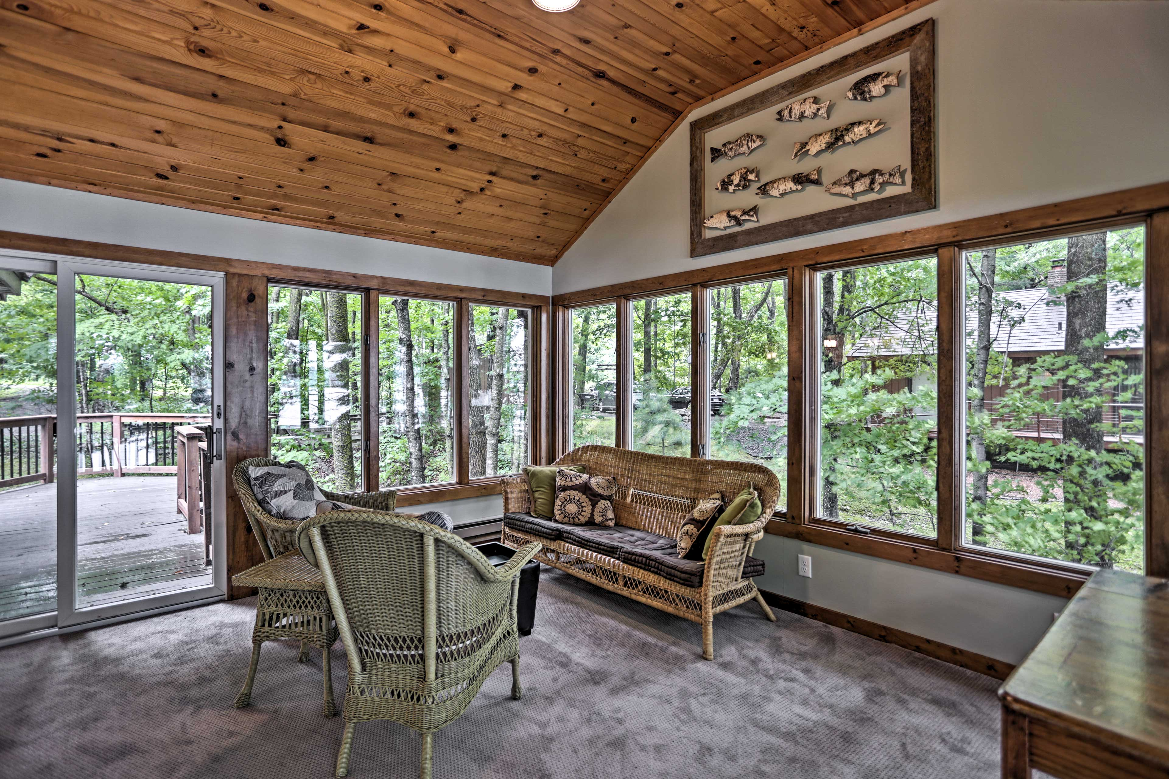 Wall-to-wall windows in the sun room provide views of the woods and lake.