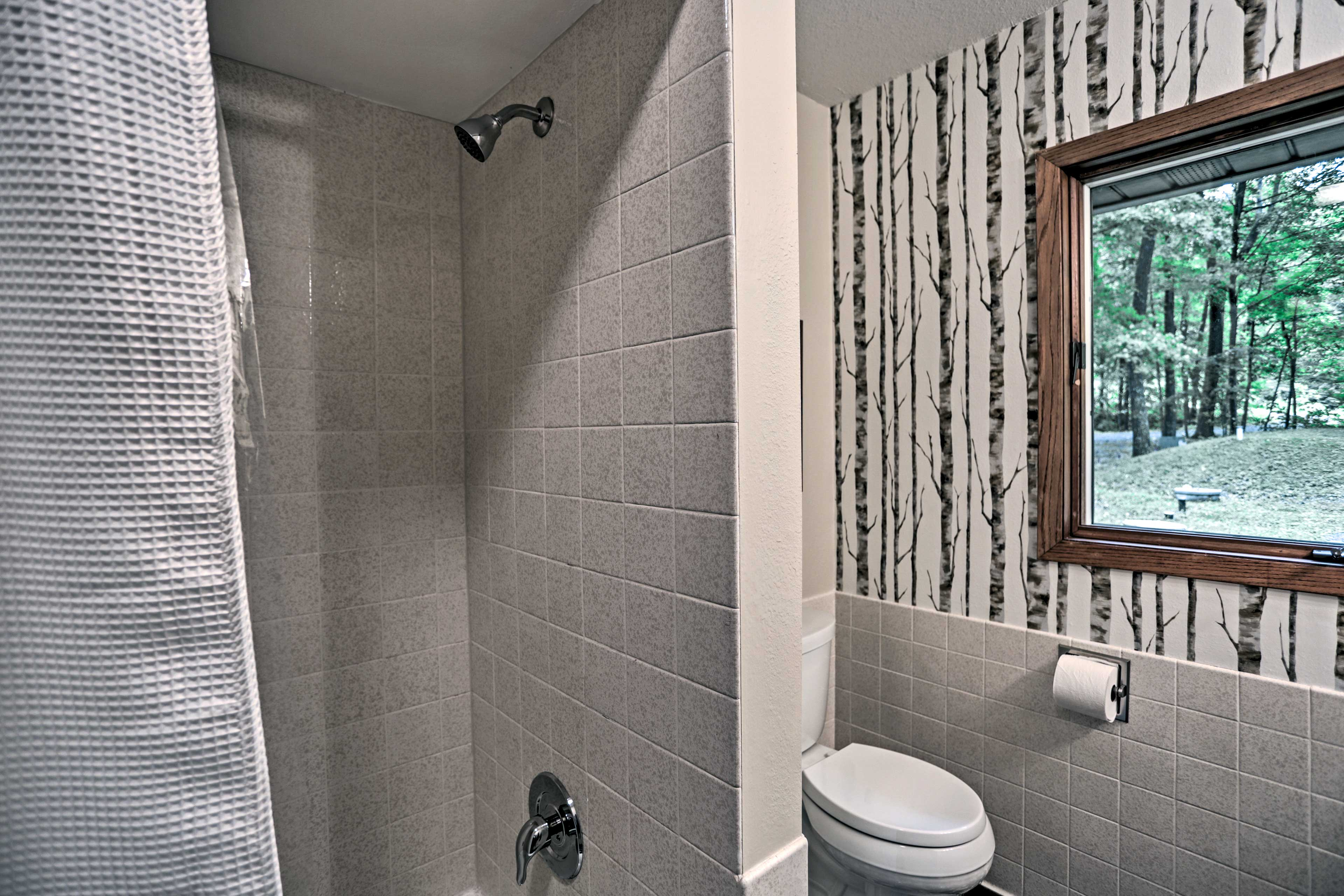 This second full bathroom hosts a shower/tub combo and birch tree wallpaper.