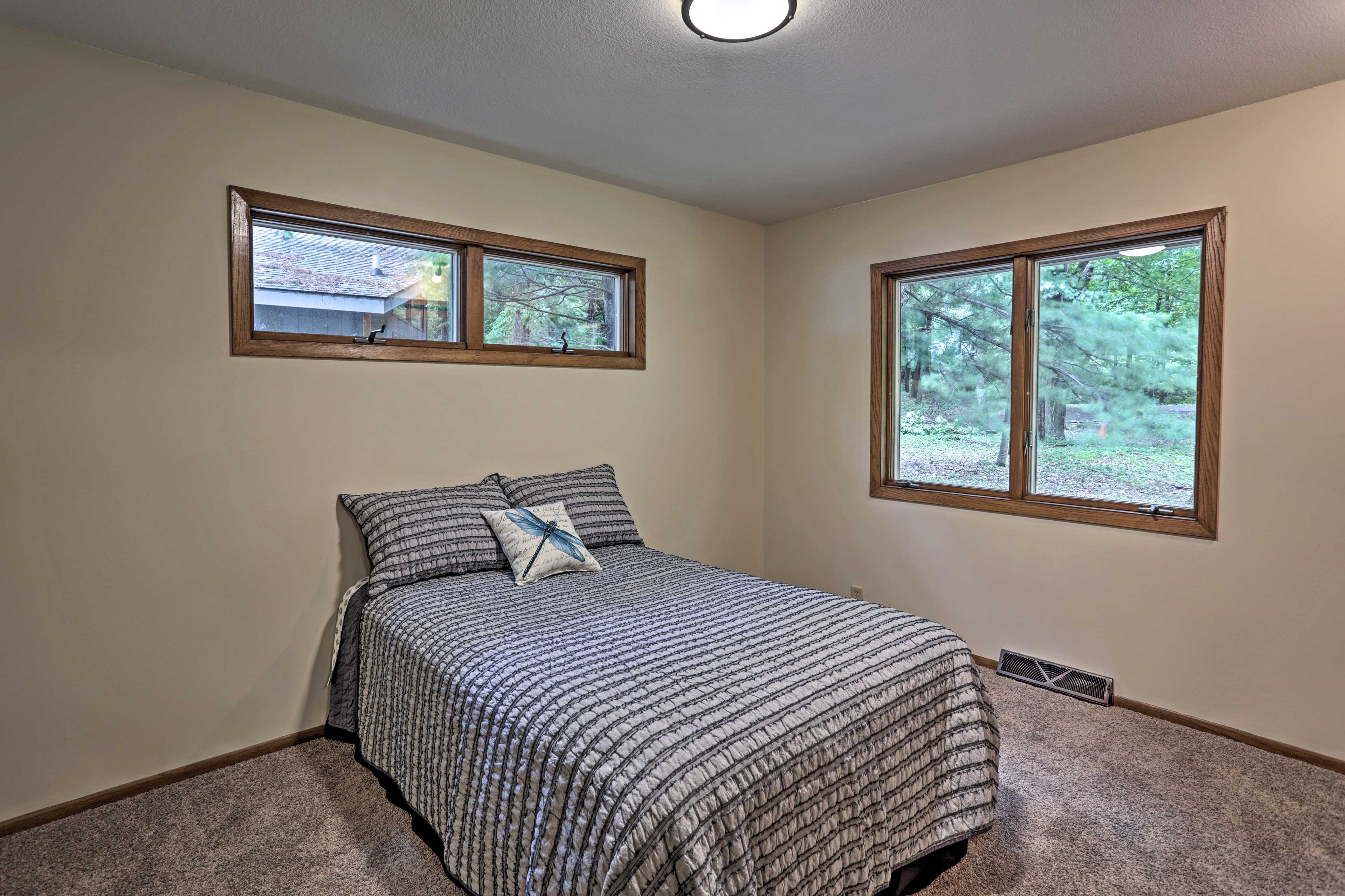 This second bedroom offers wooded views from the full bed.