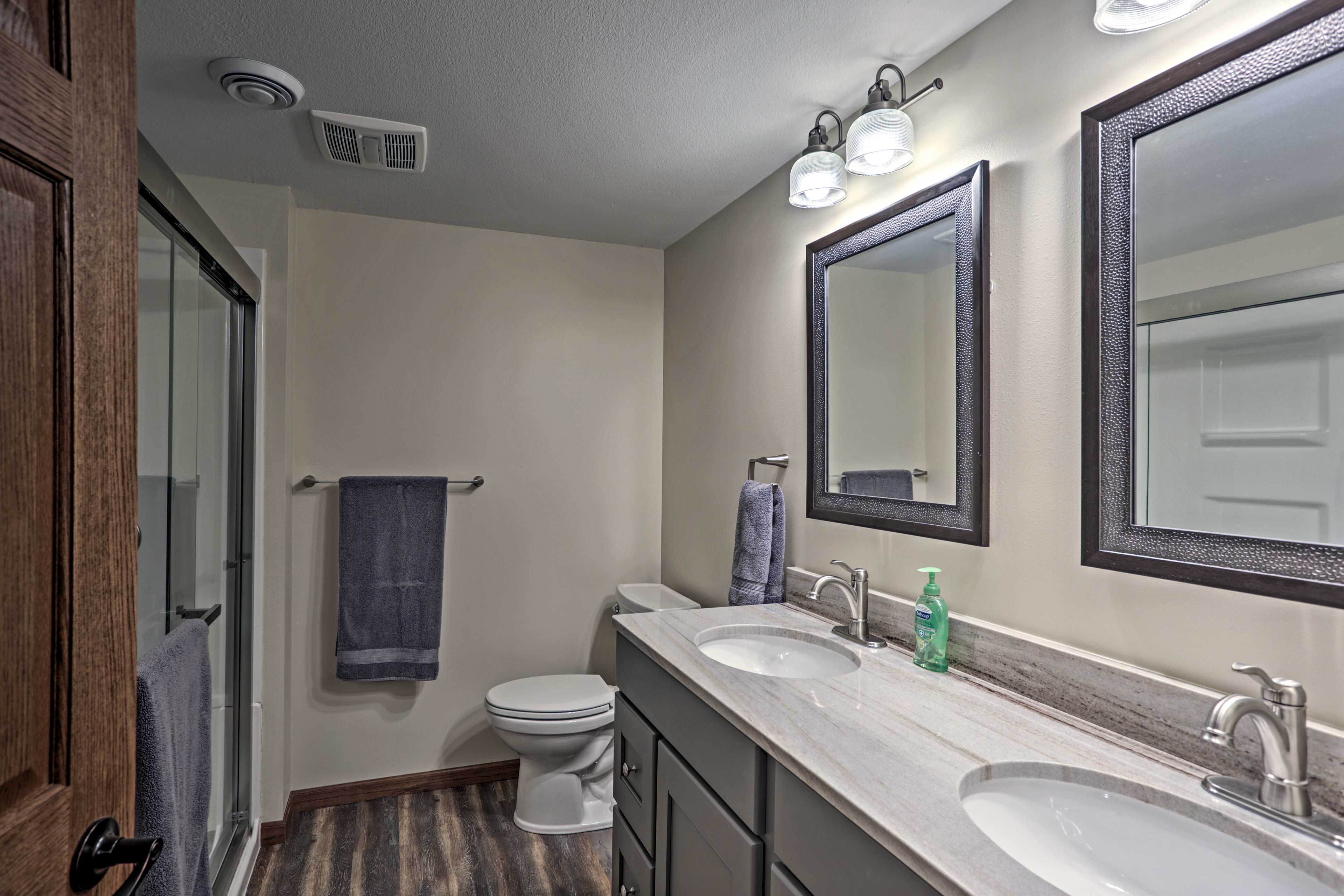 The third full bathroom features elegant double sinks and a glass shower.