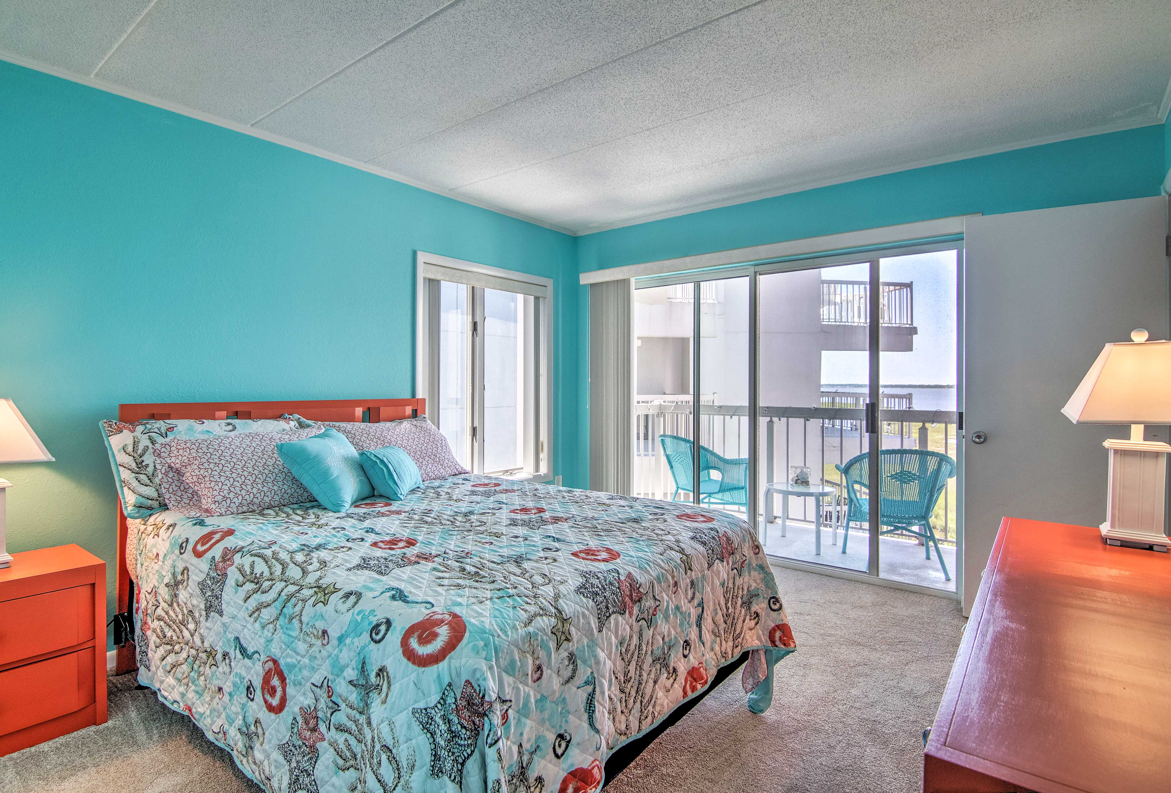 The master bedroom features a full bed, flat-screen TV, and private patio access