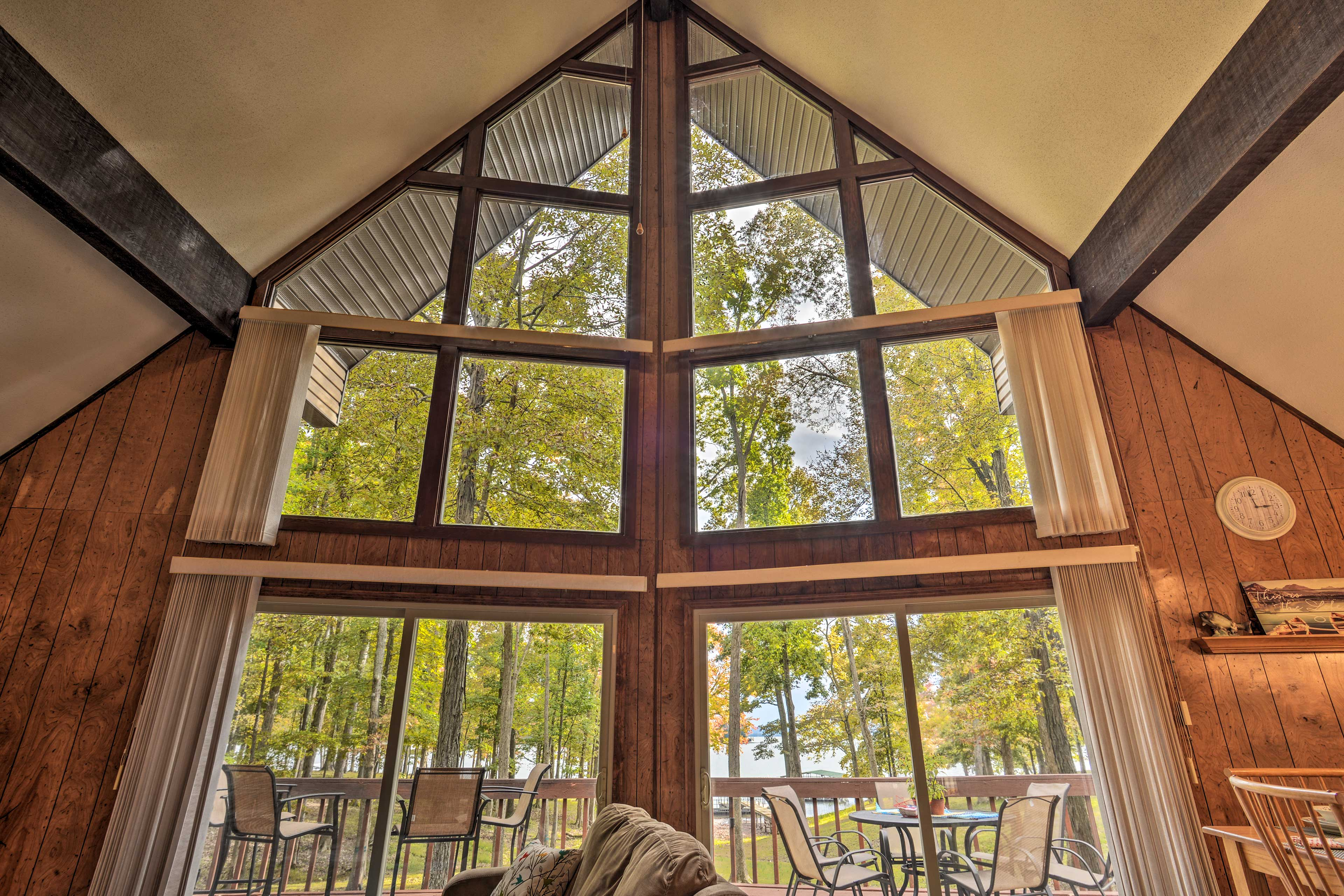 Floor-to-ceiling windows reveal the vibrant surrounding trees.