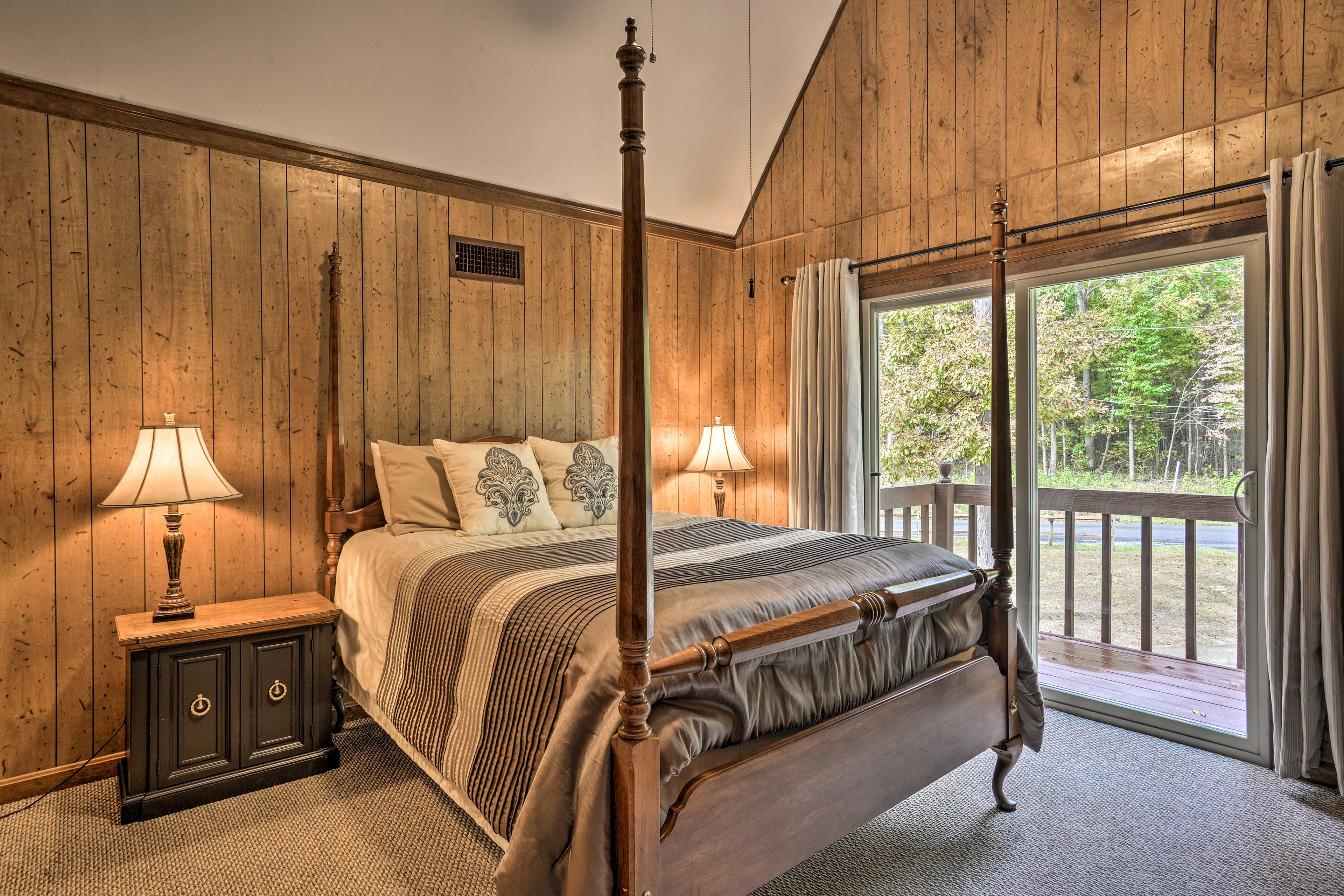 The master bedroom features a cozy queen bed and deck access.