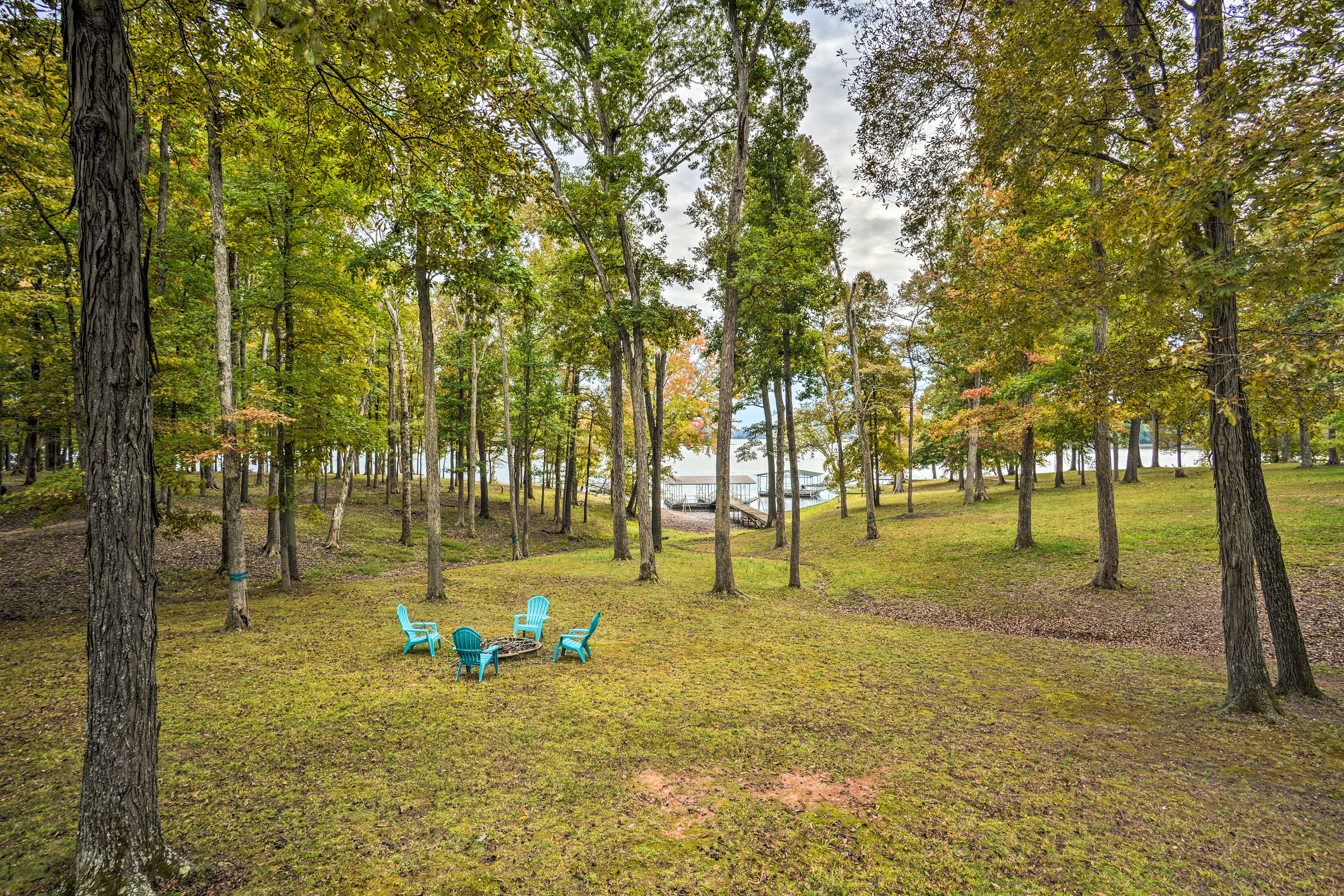 The wooded property has a fire pit on the expansive lawn.