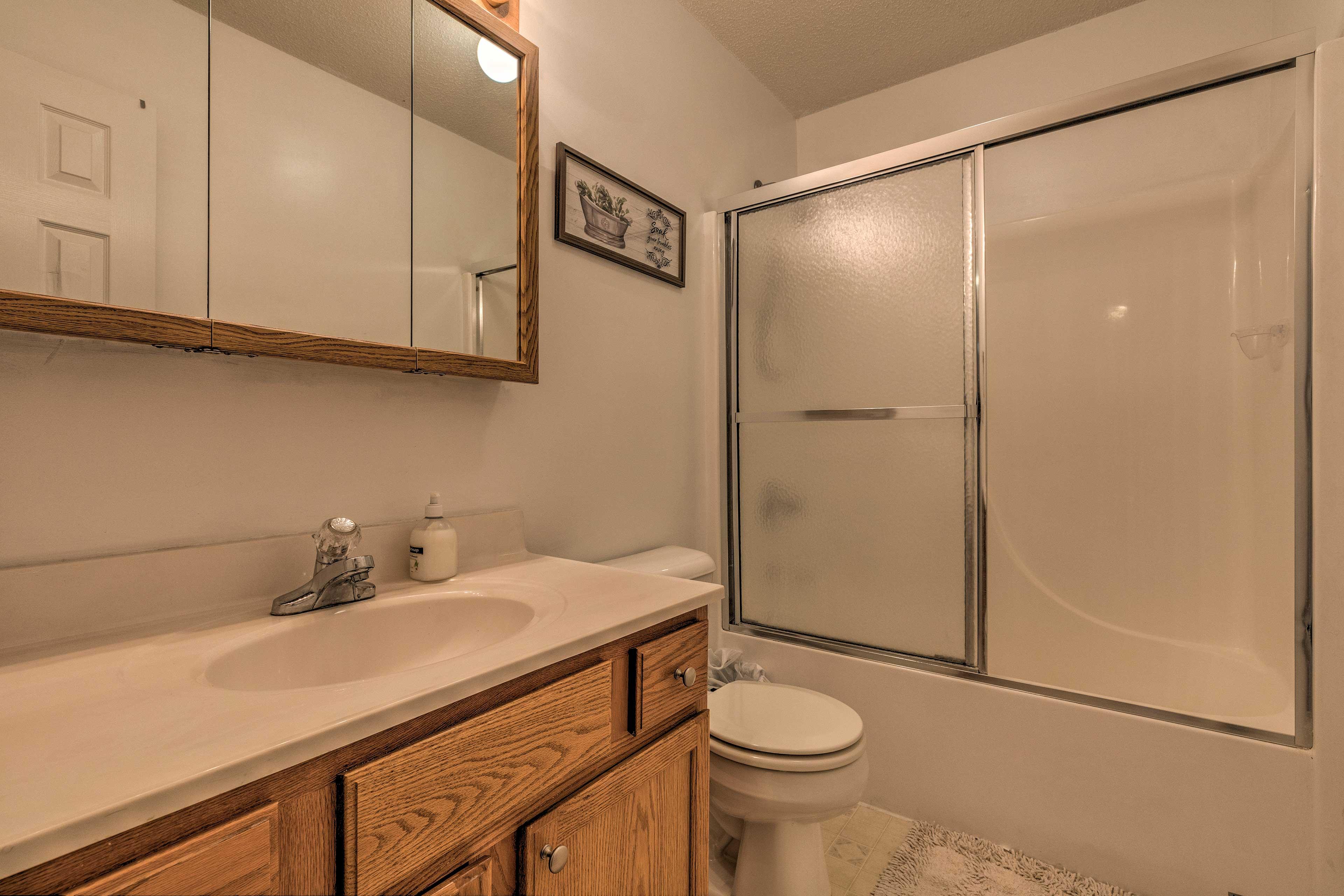 Sliding glass doors line this shower/tub combo in this full bathroom.