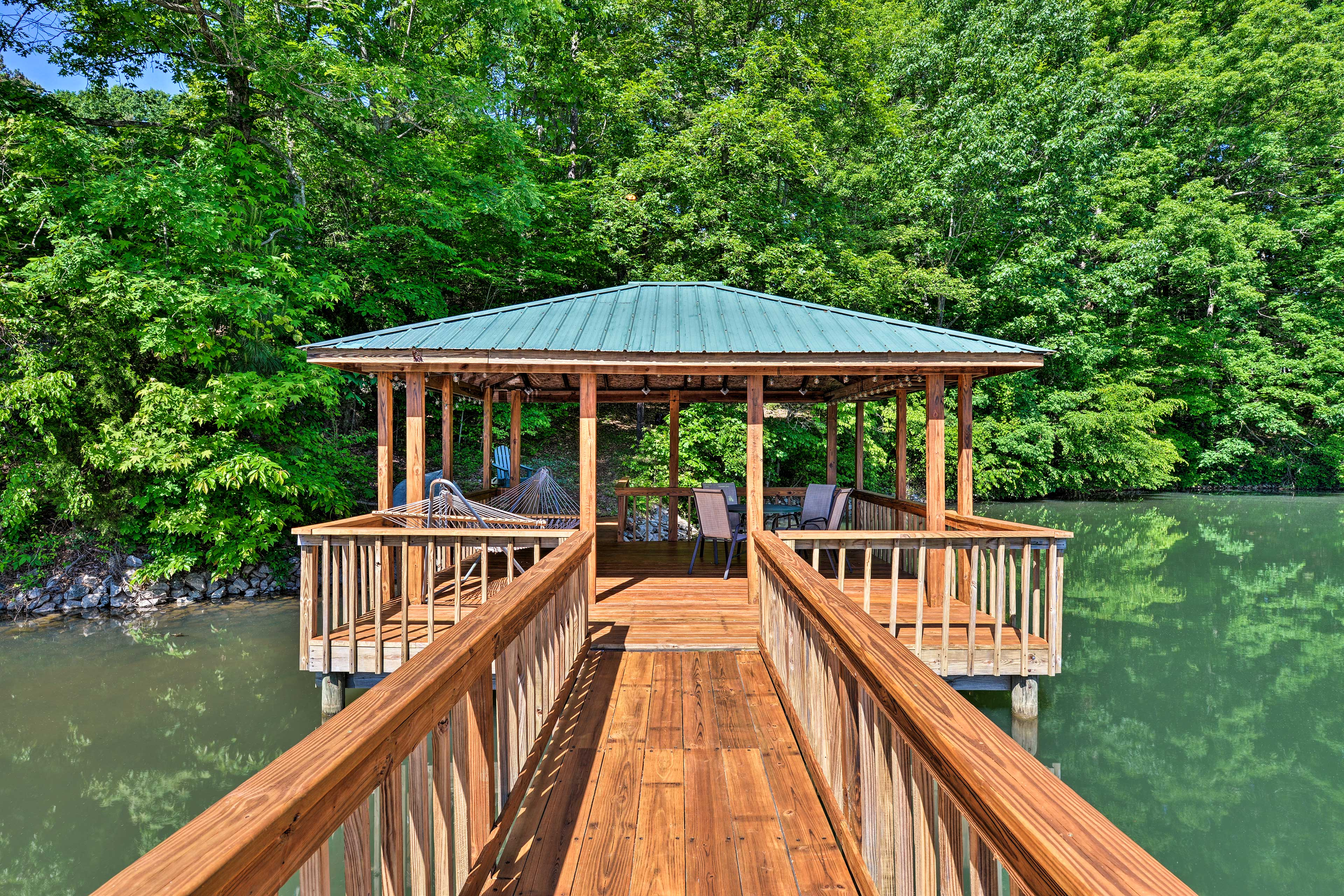 The covered portion of the dock has lights, a hammock, and a dining area.