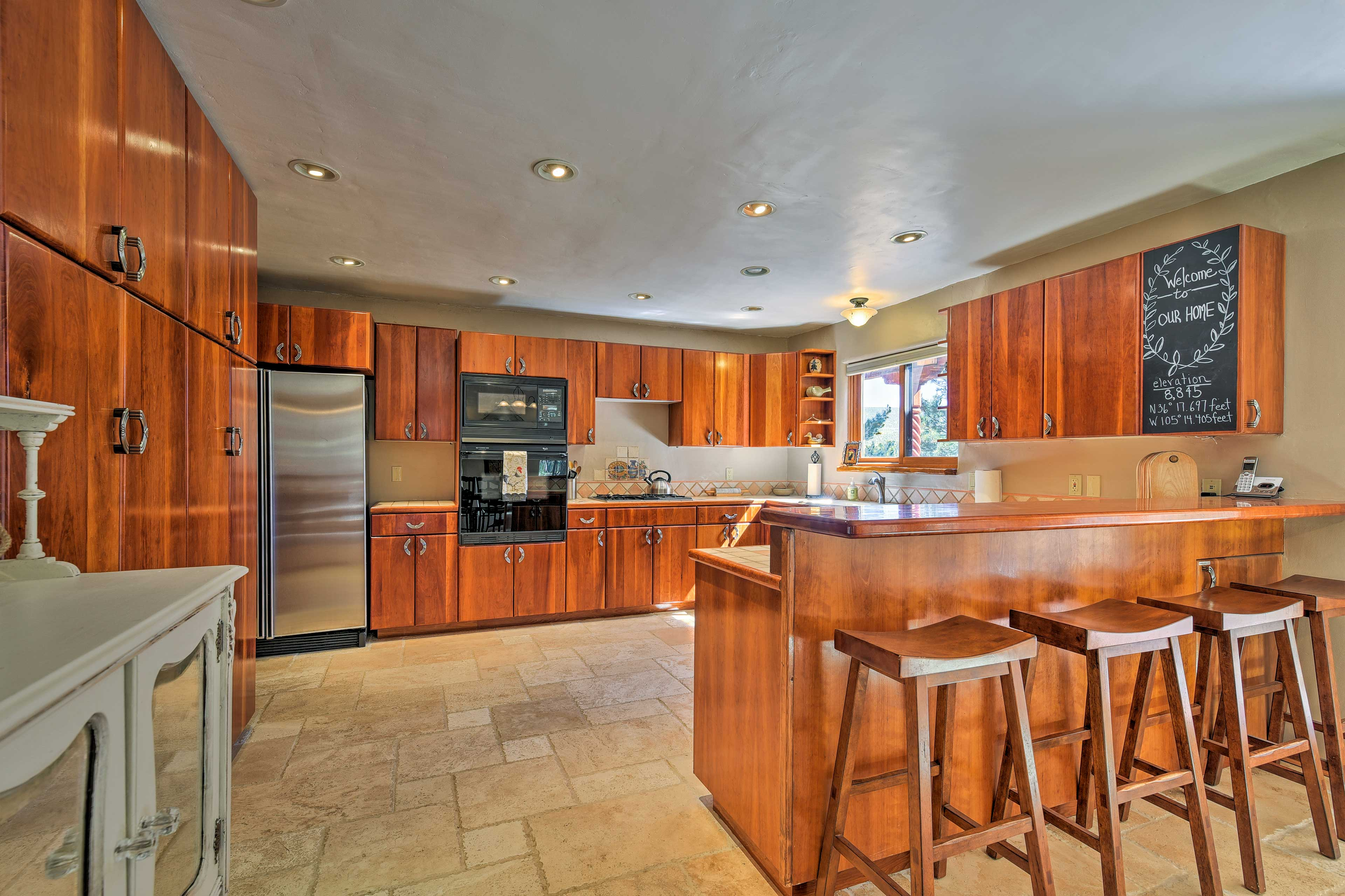 Tiled floors and sleek wooden cabinets detail the fully equipped kitchen.