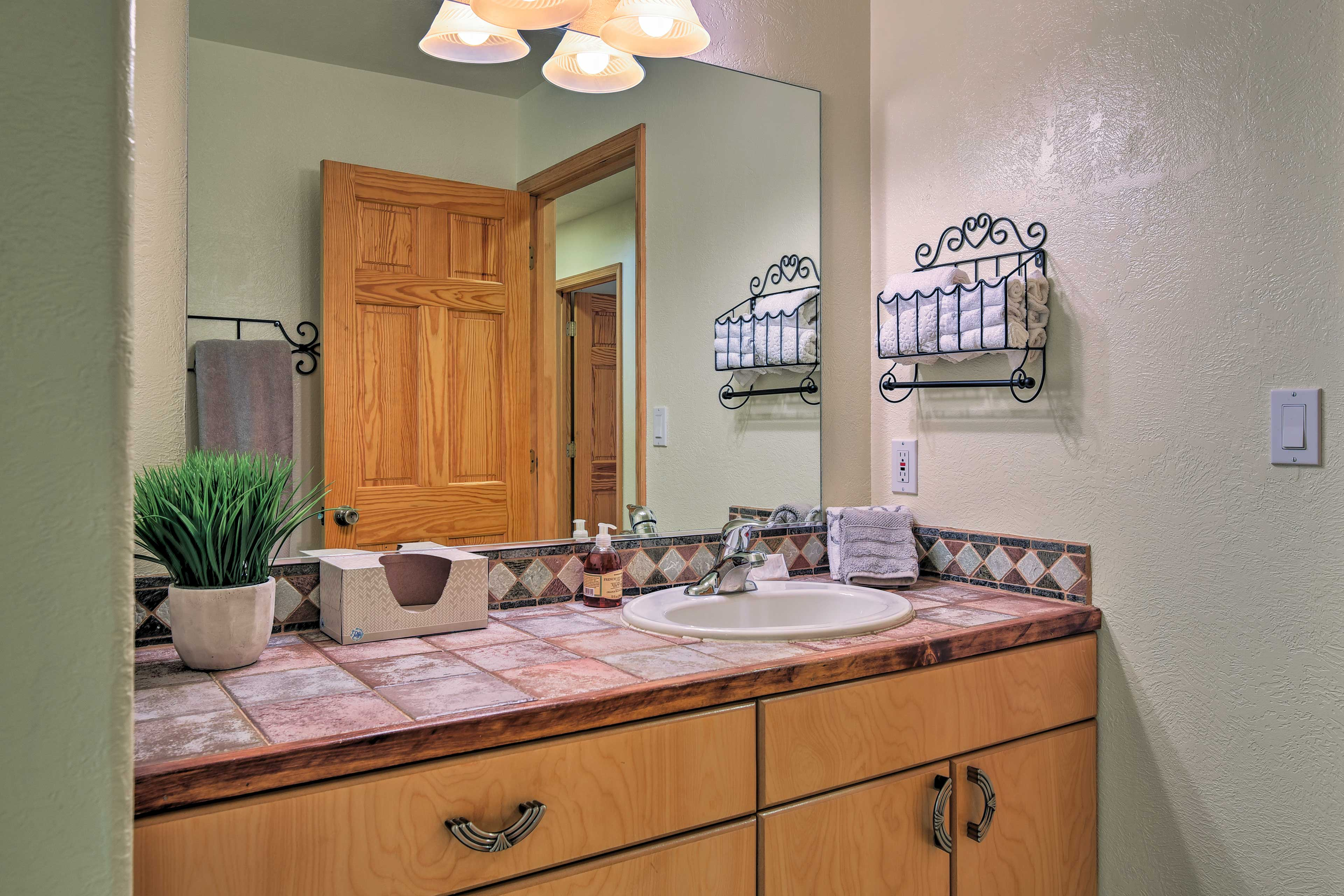 The en-suite bathroom features a shower/tub combo and rustic tile accents.
