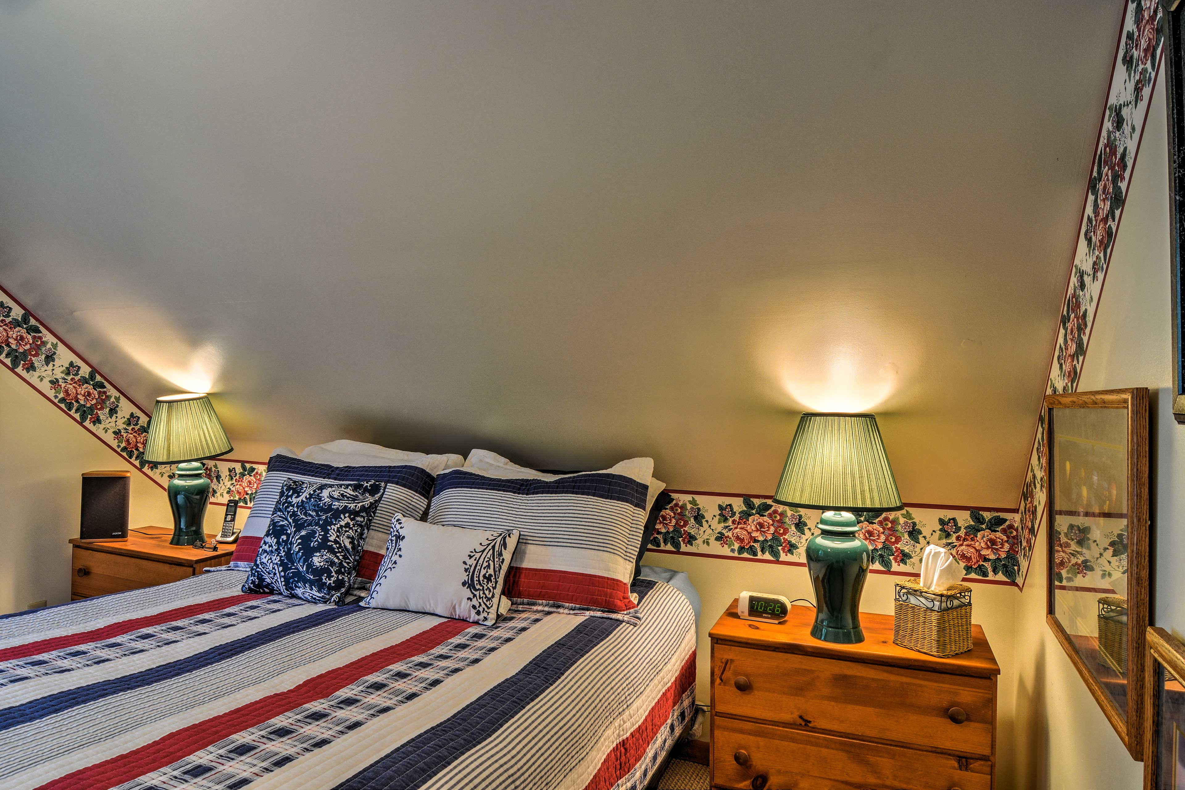 Upstairs, the master bedroom boasts a plush queen bed.