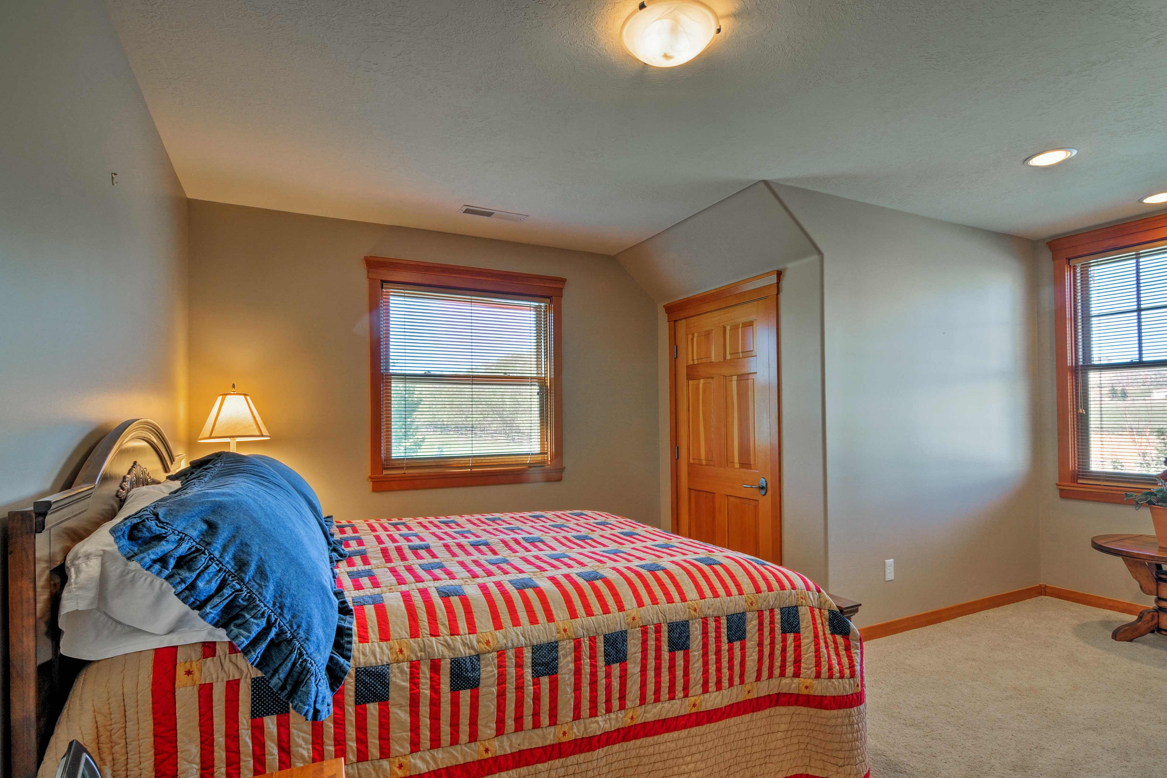 The fourth bedroom features a queen-sized bed & numerous windows!