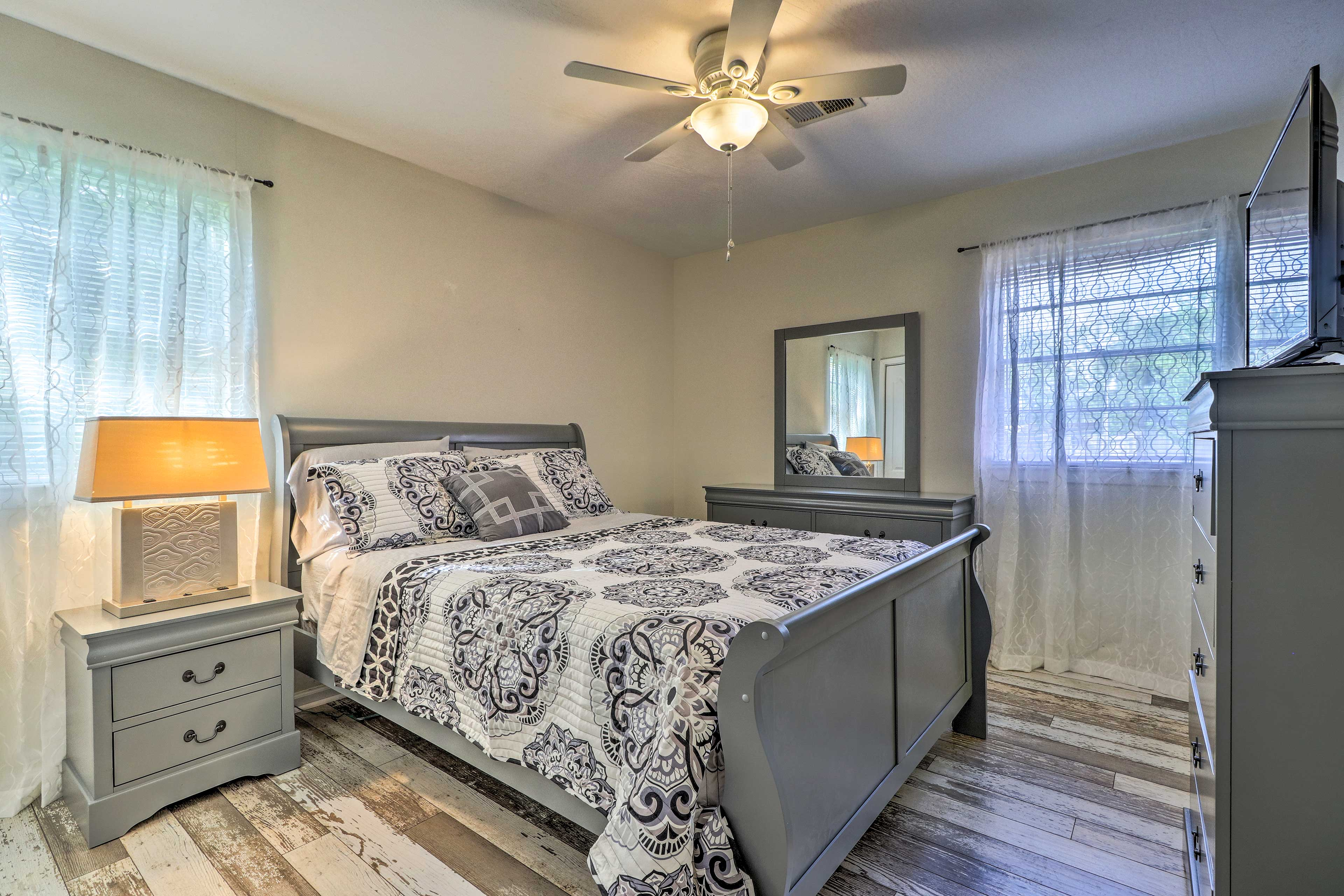 The master bedroom features lovely grey furniture & a matching bedspread.