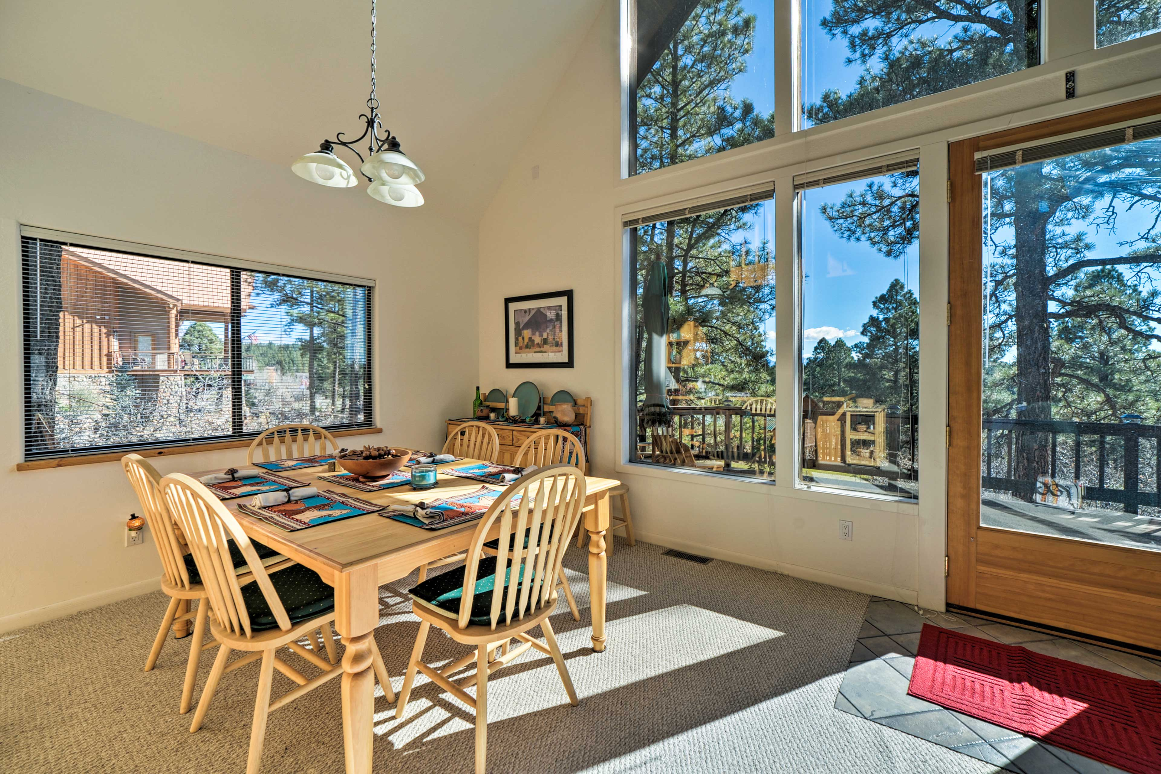 The home is surrounded by towering pine trees.
