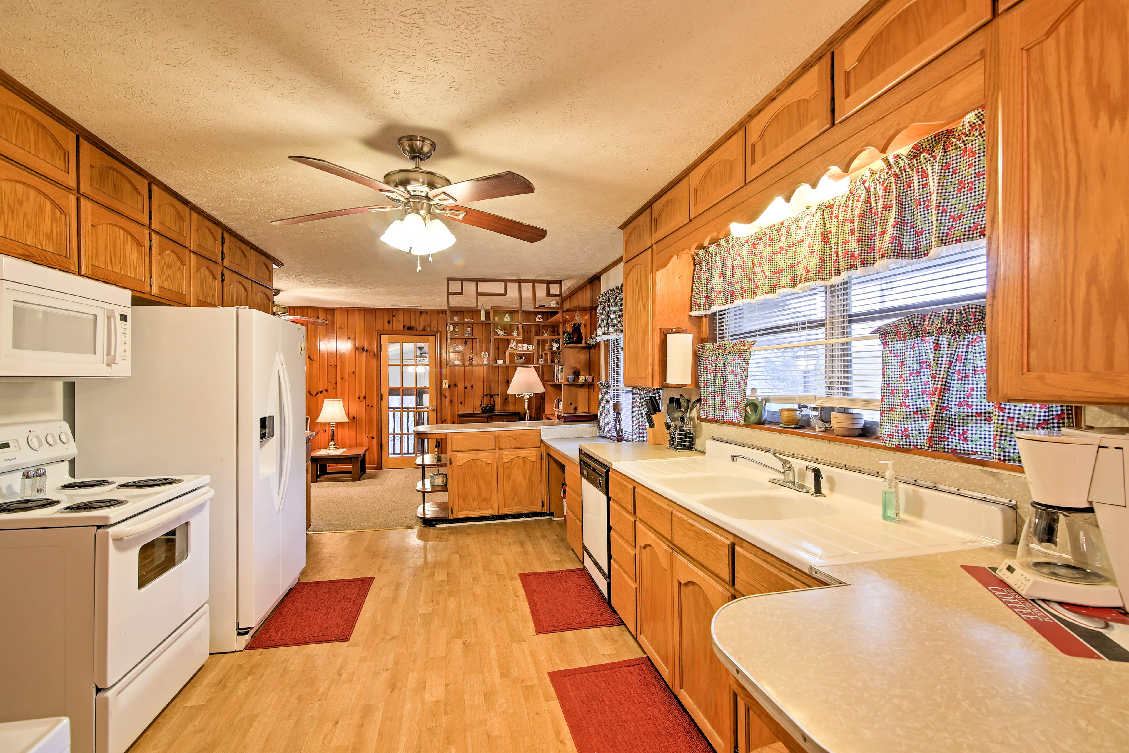 Hardwood floors and broad picture windows detail the fully equipped kitchen.