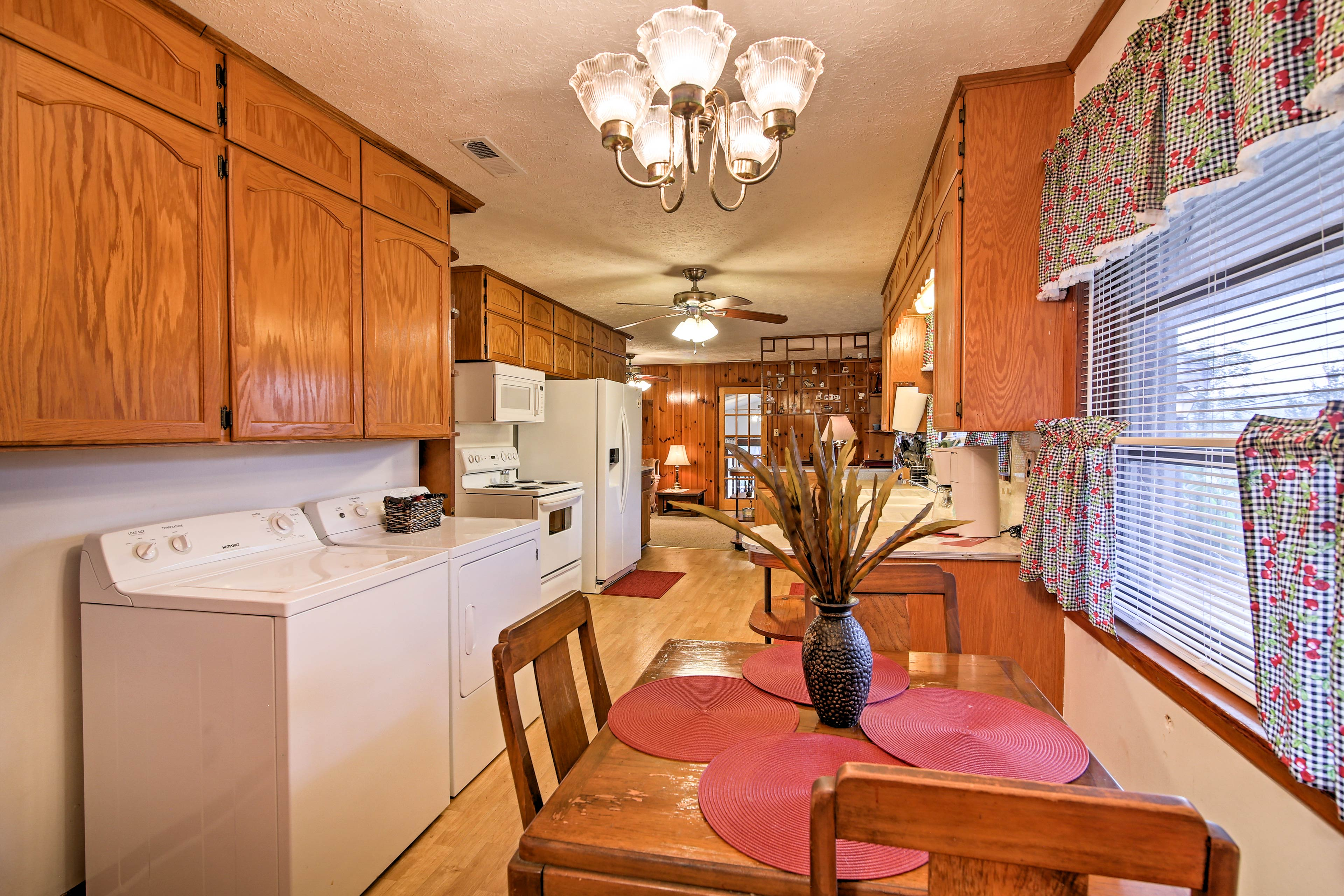 A 3-person kitchen table rests beside the washer and dryer.