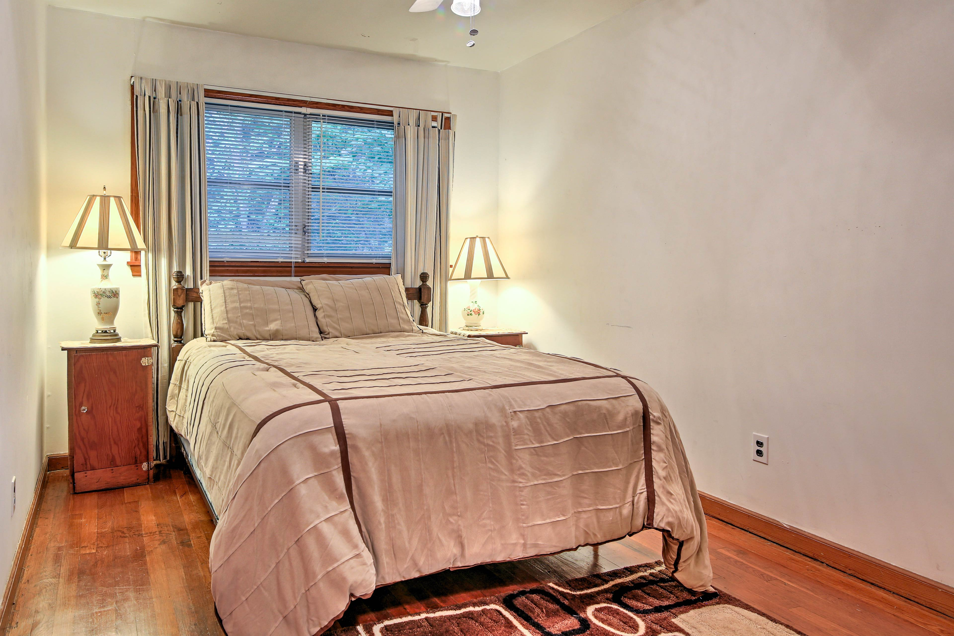 The third bedroom hosts a queen bed and bright natural light.