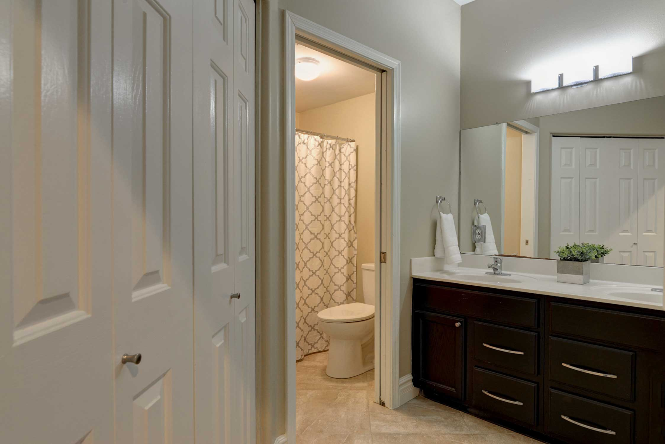 This bathroom includes a large vanity with 2 sinks.