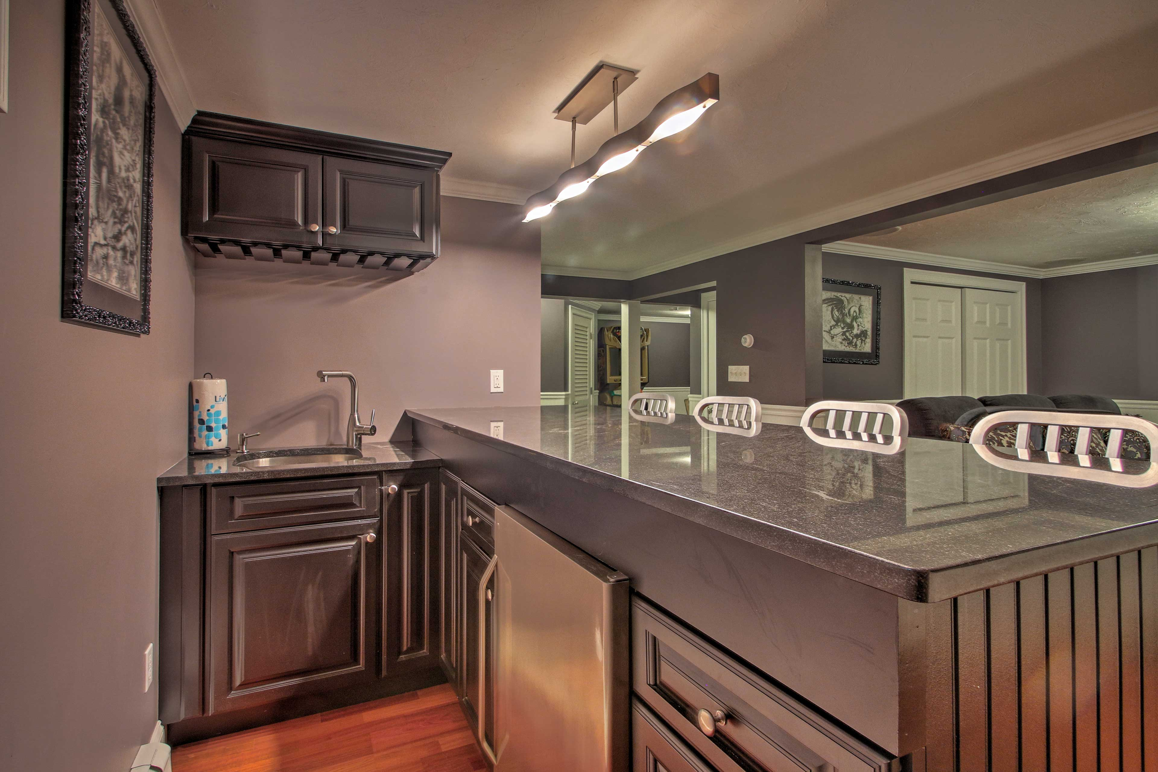 The area also features a full bar with a mini-fridge and wine cooler!