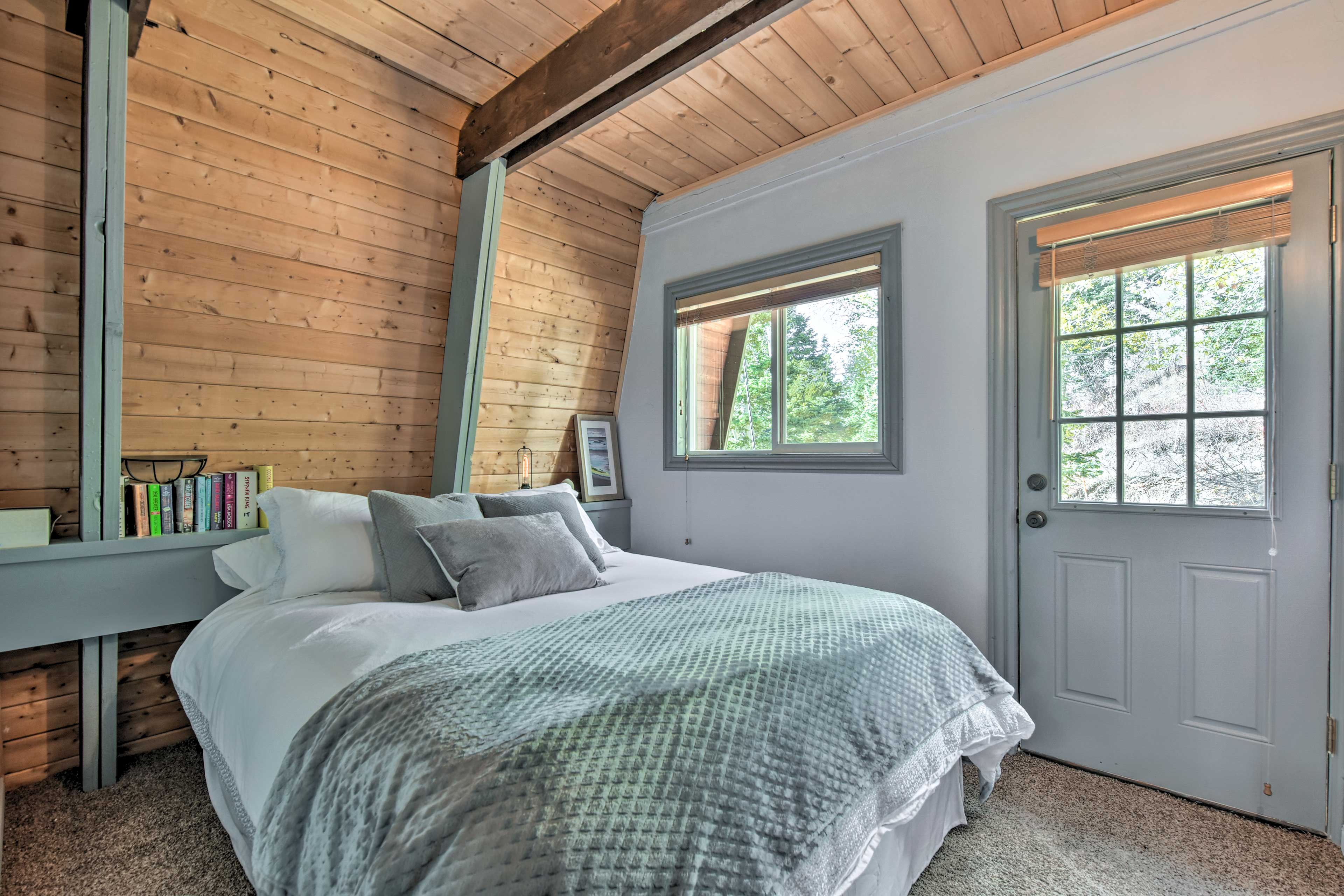 This first bedroom contains a queen bed and access to a private balcony.