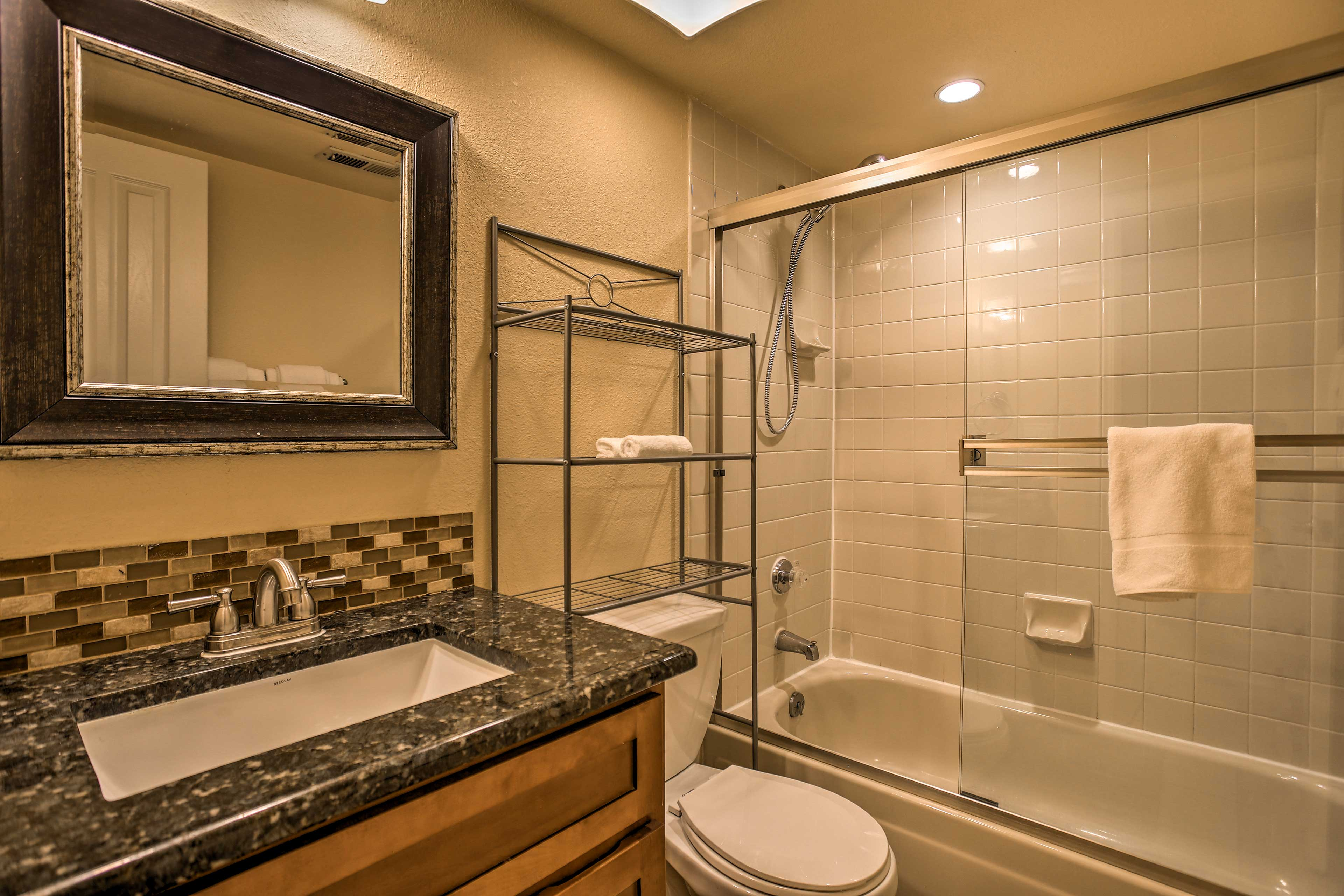 The first bathroom is equipped with a shower/tub combo.
