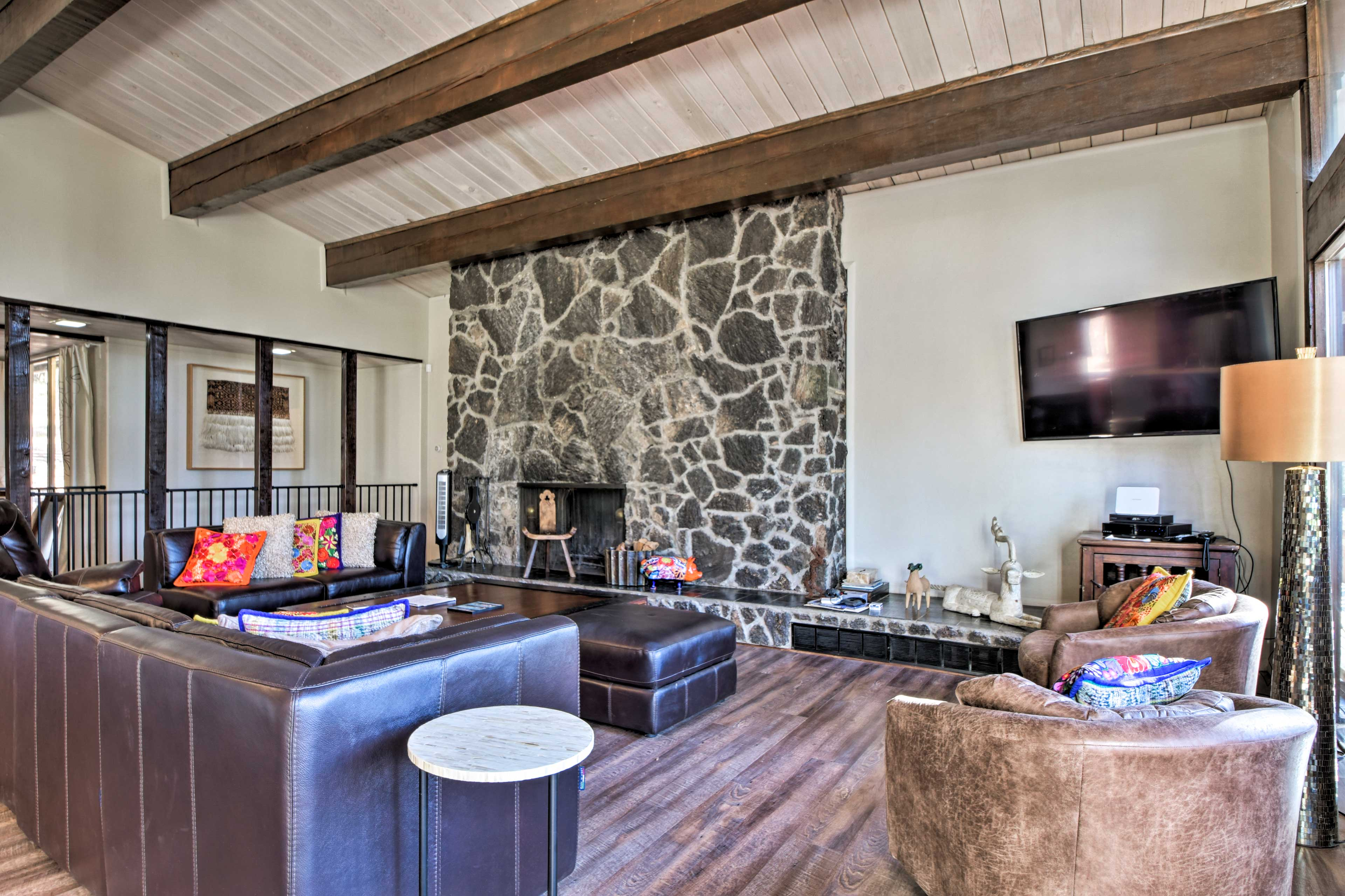 Sunlight, mountain and forest views pour into the inviting living area.