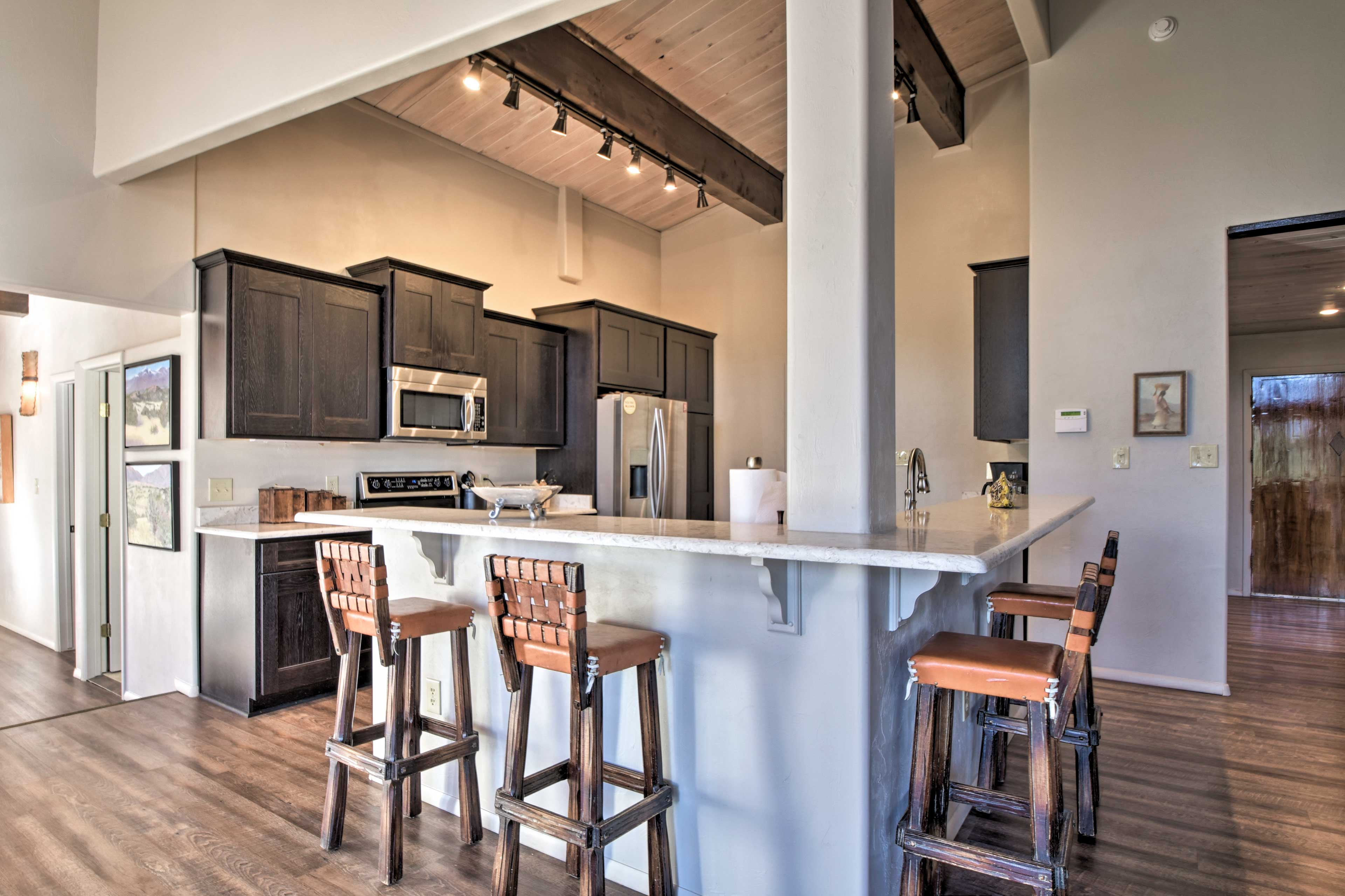 Just steps away, the kitchen features 4 chairs at the breakfast bar.
