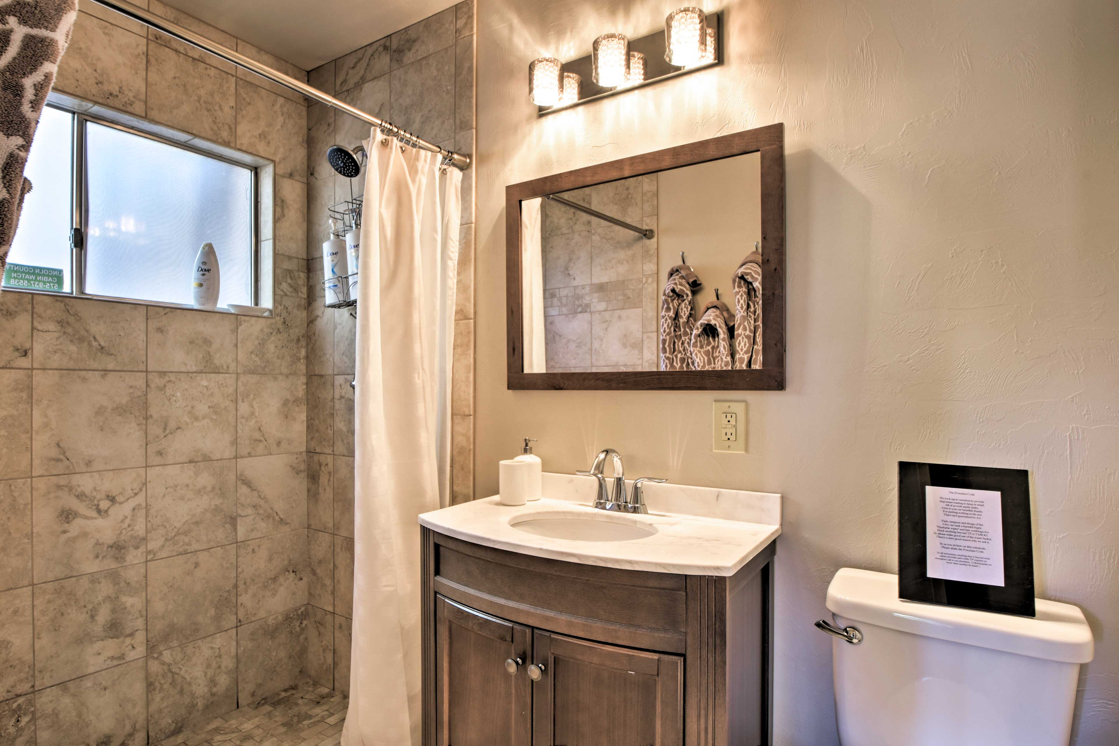 This tiled walk-in shower and full bathroom is just steps away.