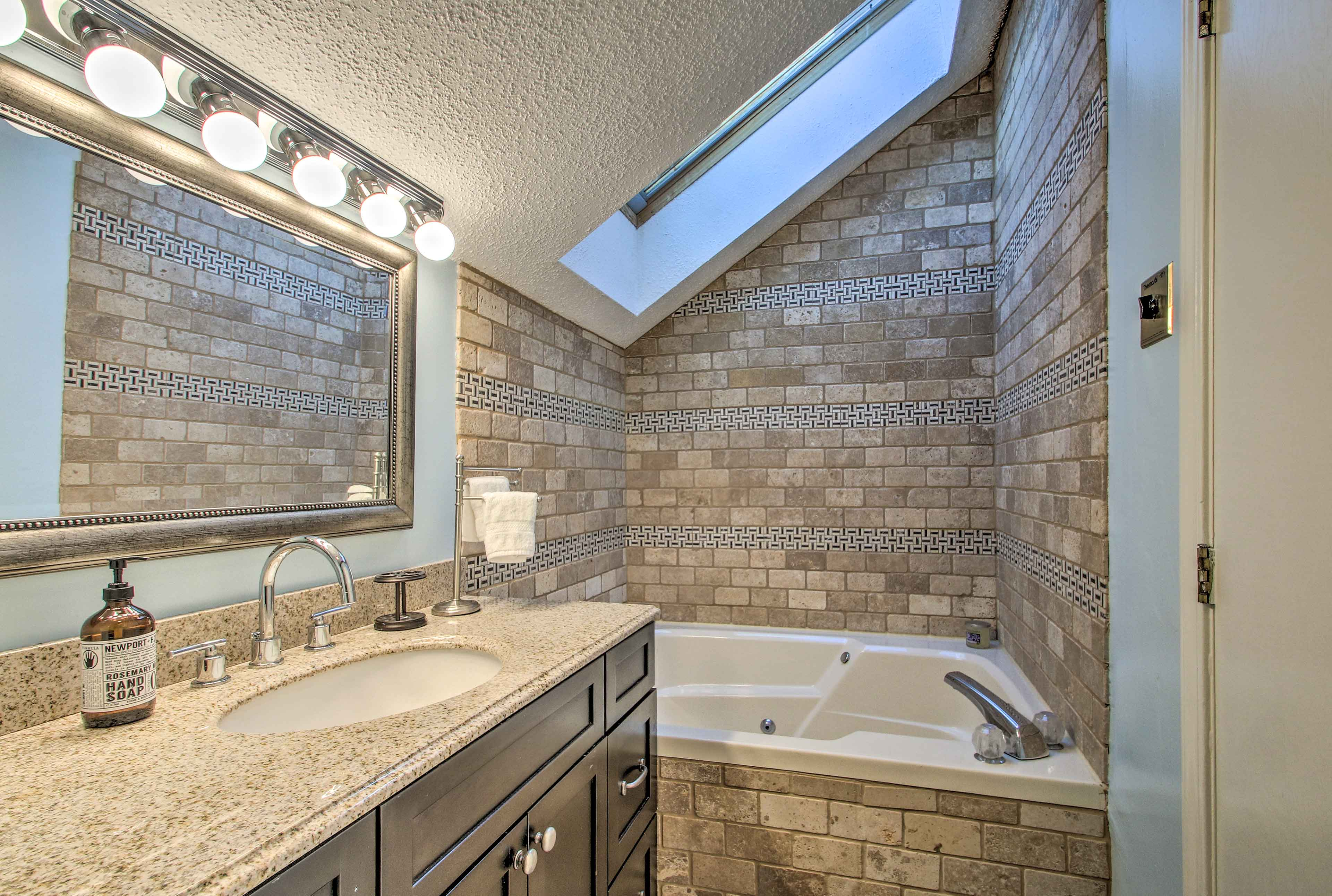 Treat yourself to a soak in the 2-person Jacuzzi tub under the skylight.