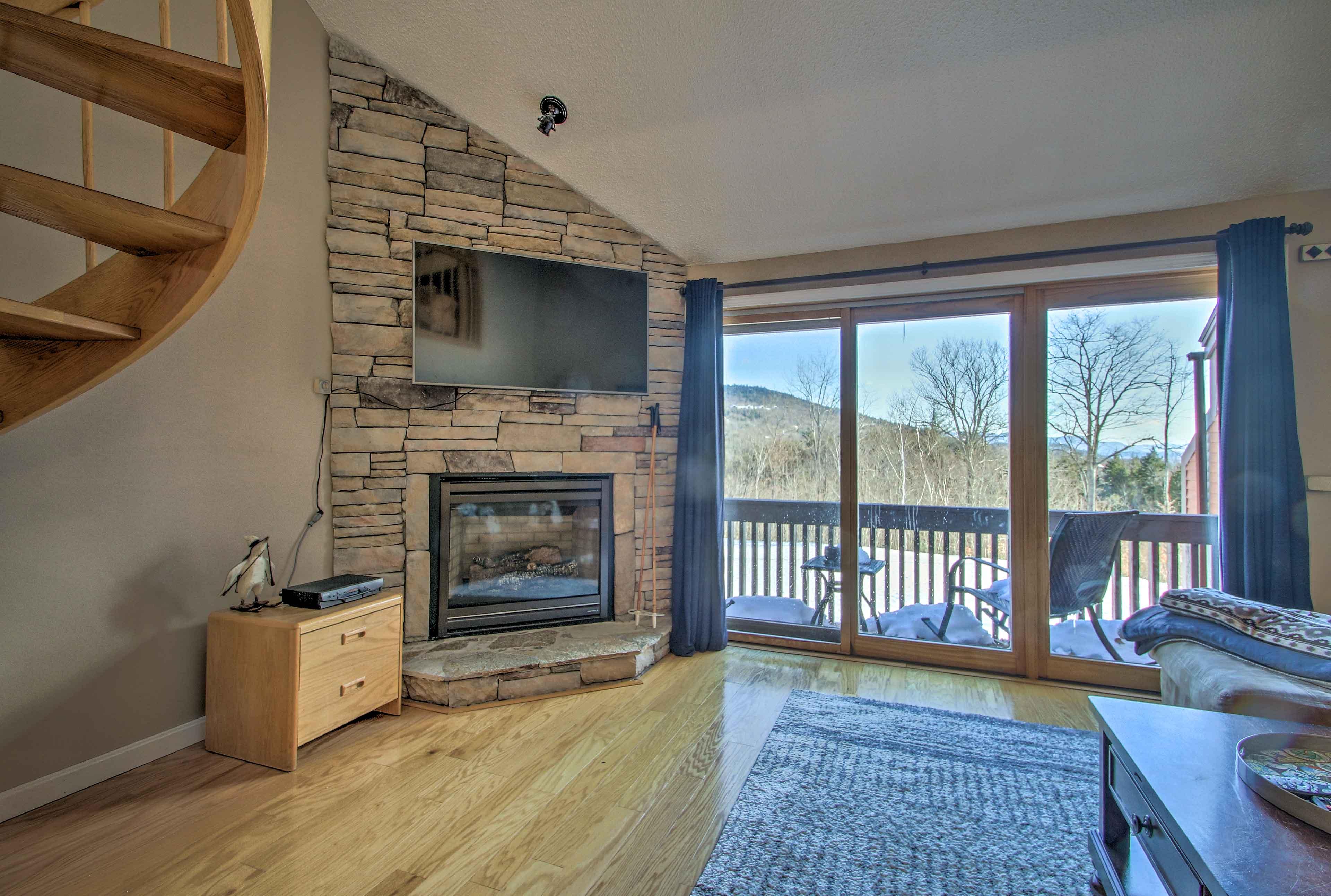 Unwind beside hardwood floors, a charming stone fireplace and mountain views.