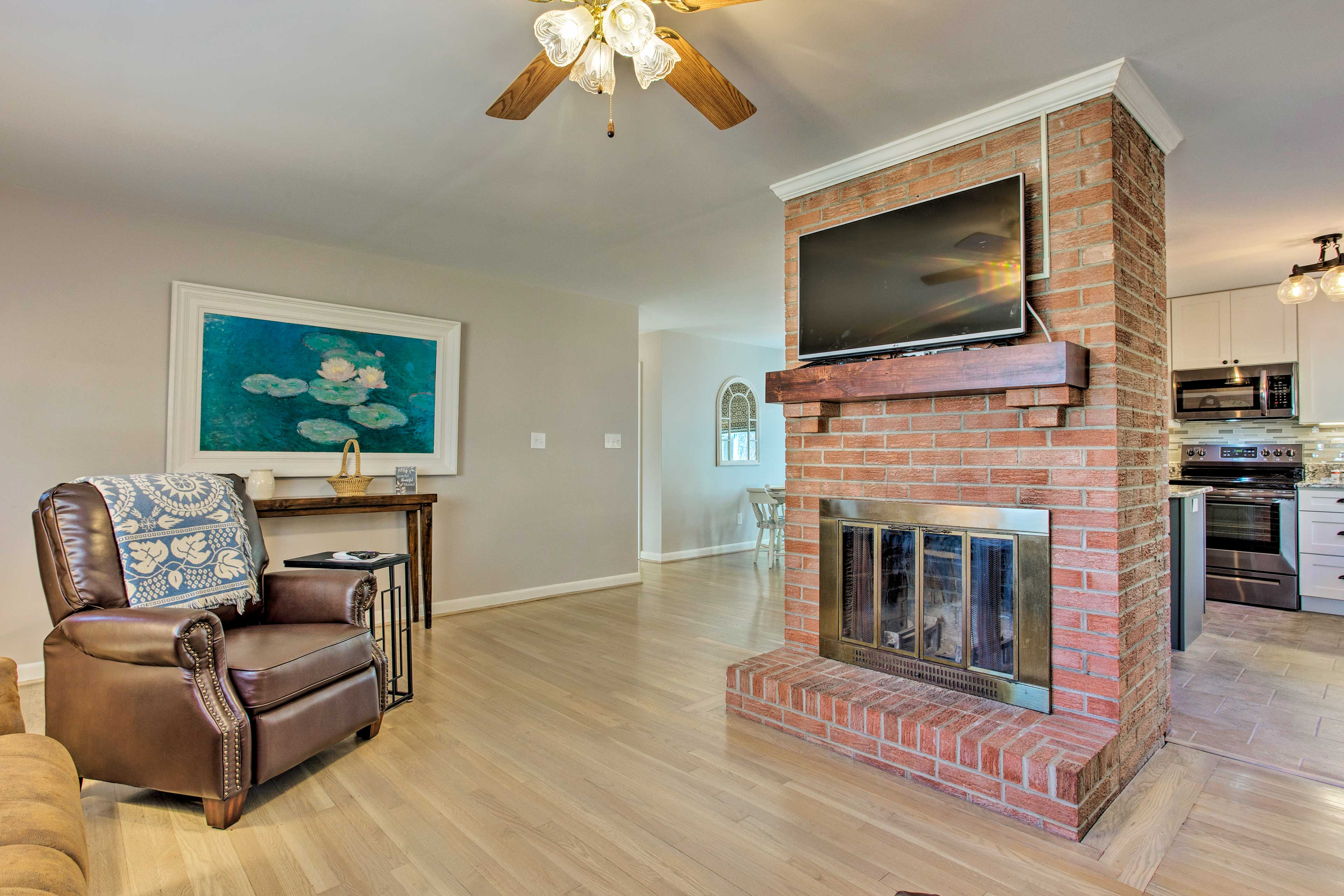 A brick wall with a mounted cable TV serves as the room's focal point.