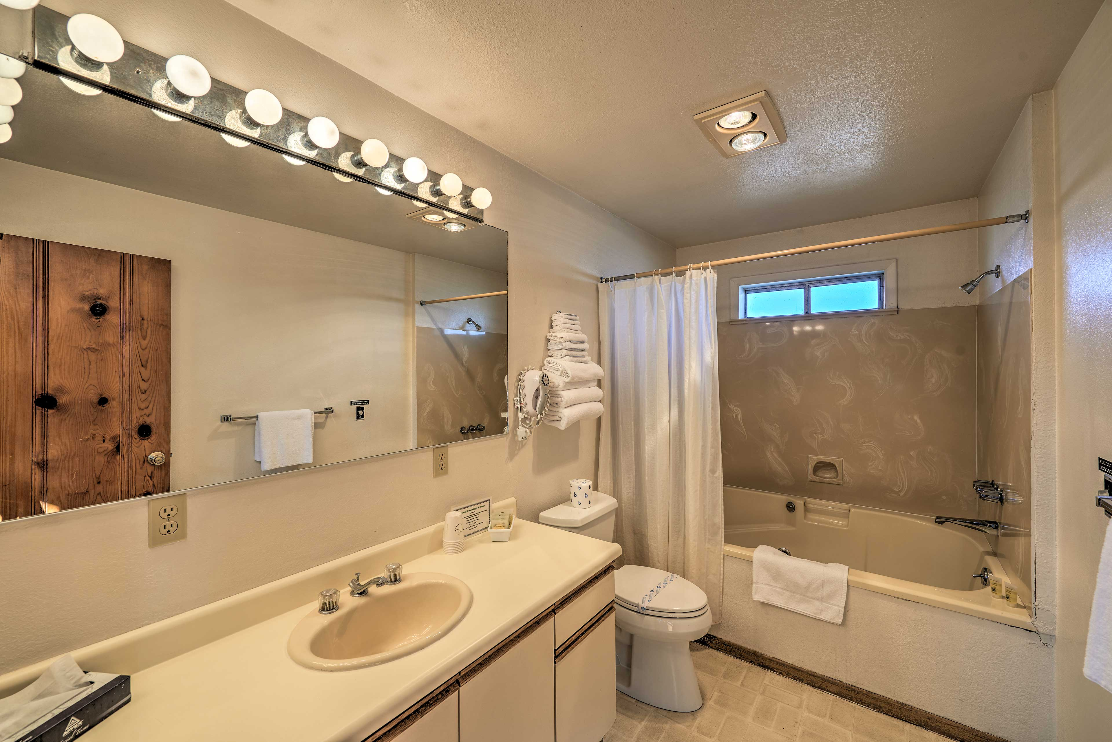 This spacious bathroom comes equipped with towels.