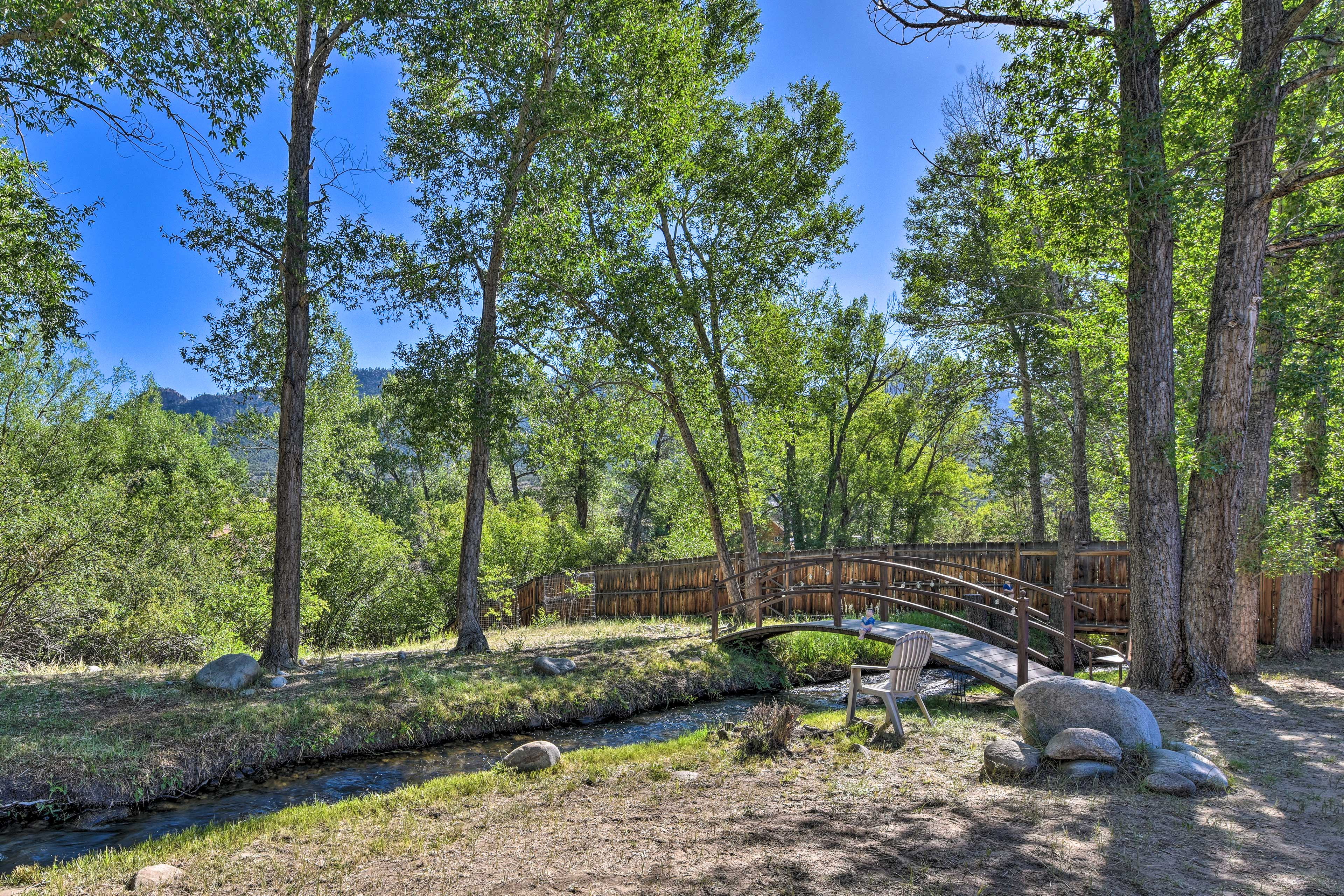 The home sits on a fenced-in yard near Cottonwood Creek with numerous trees.