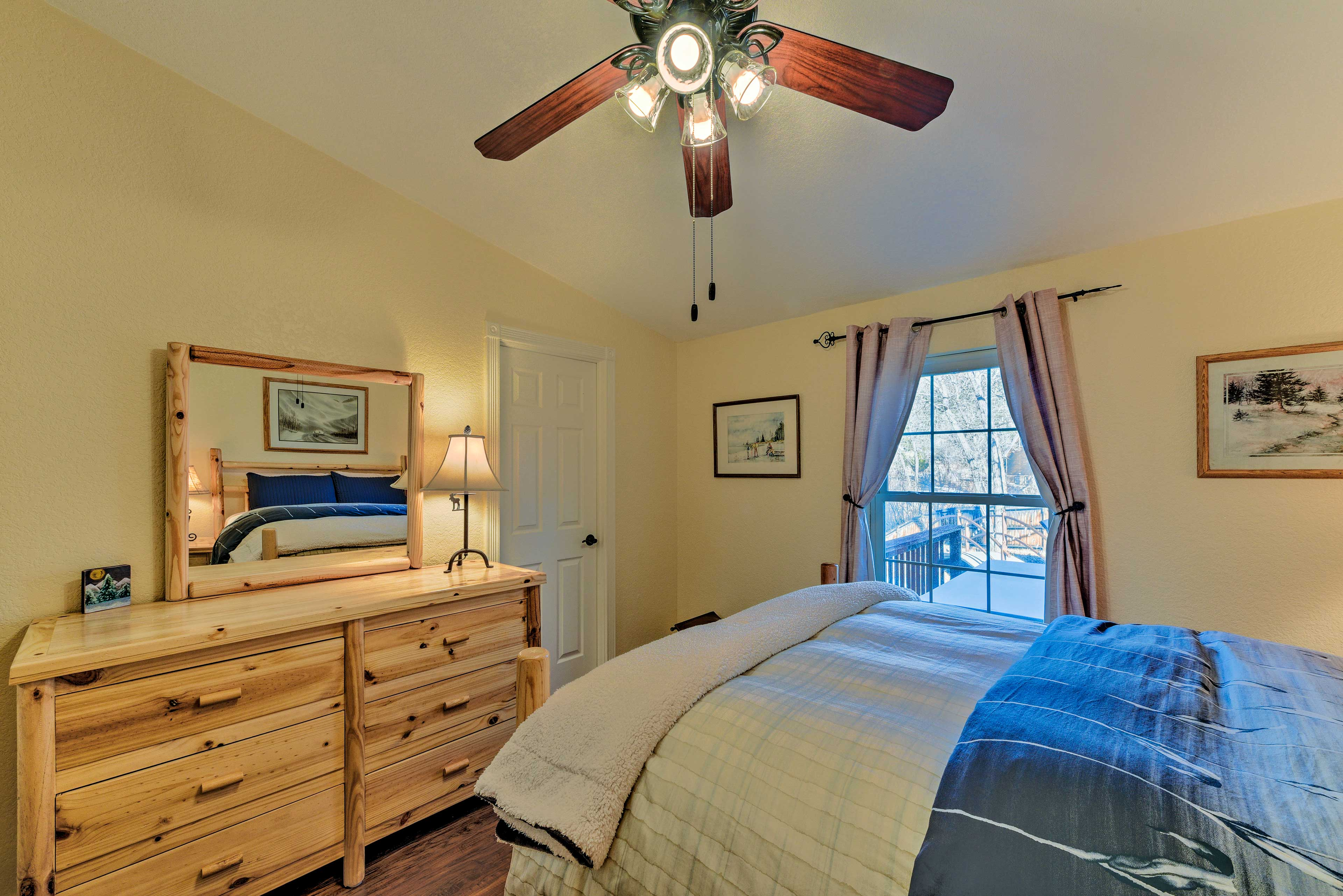 The second bedroom includes a large wood dresser & deck-facing picture window.