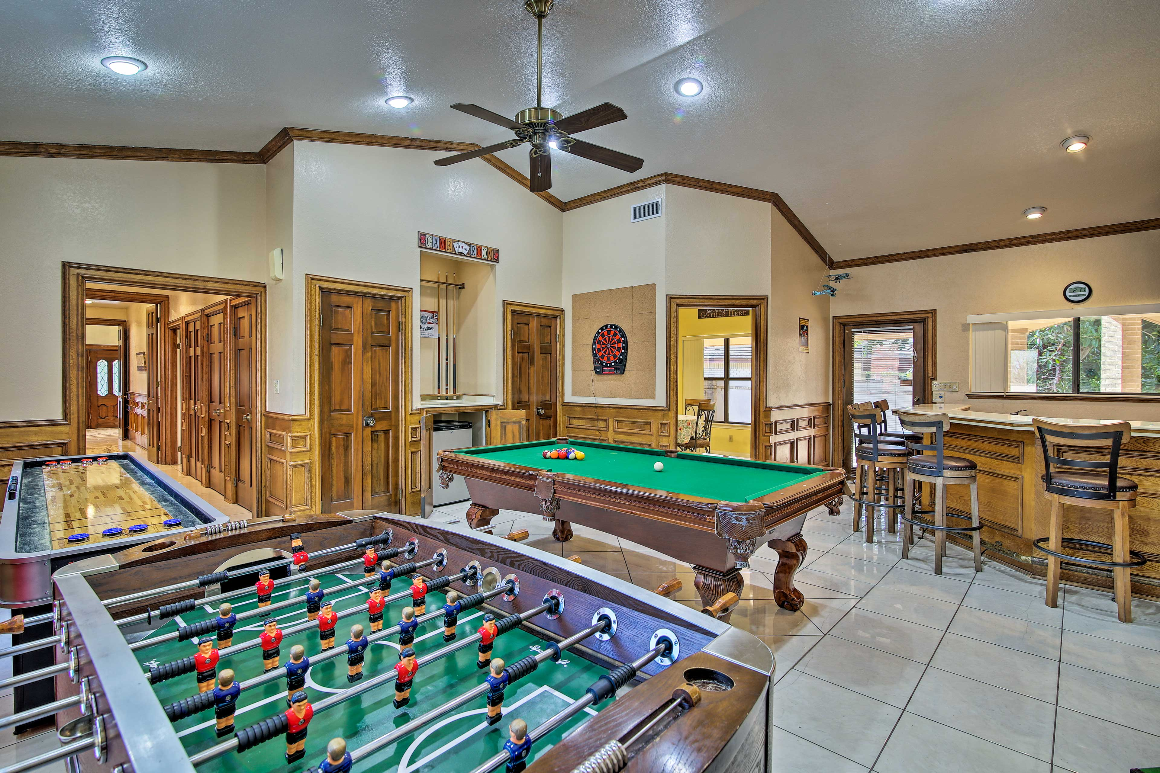 This game room is complete with a shuffleboard, foosball and pool table!
