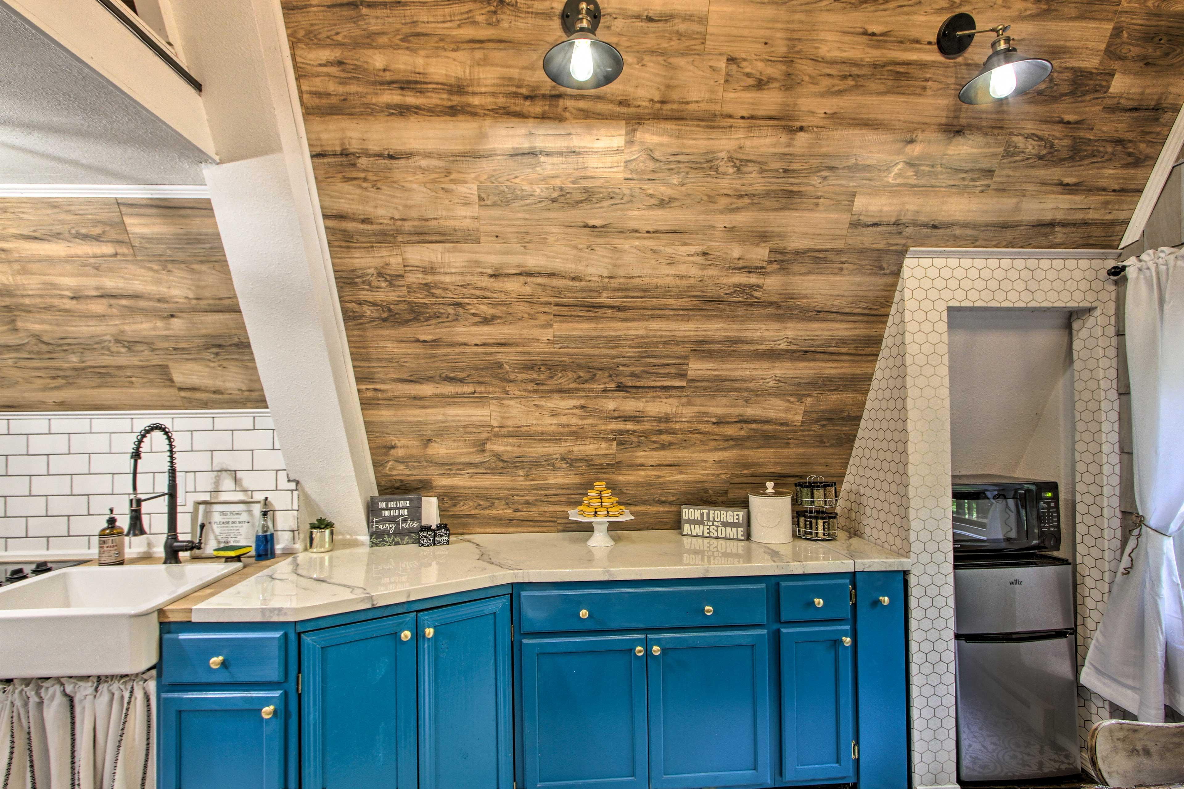 The kitchen also includes a stove/oven, farmhouse sink, microwave, & mini-fridge