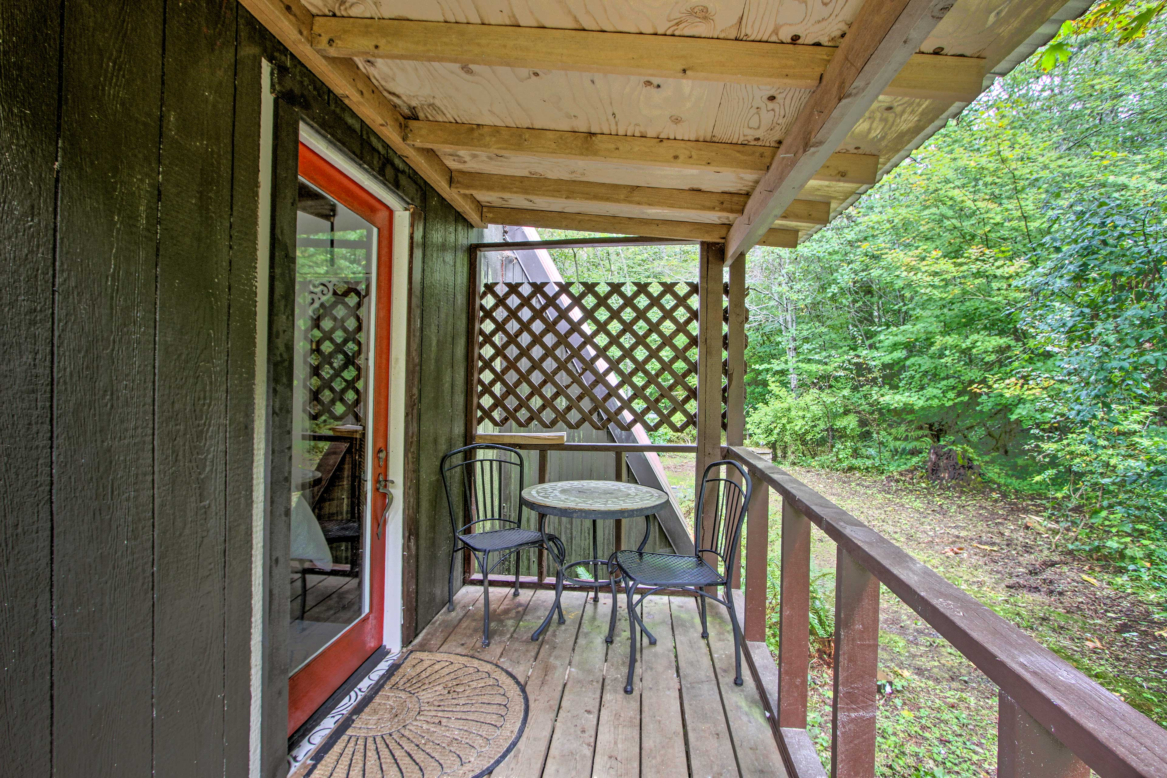 The covered deck houses a 2-person bistro table.