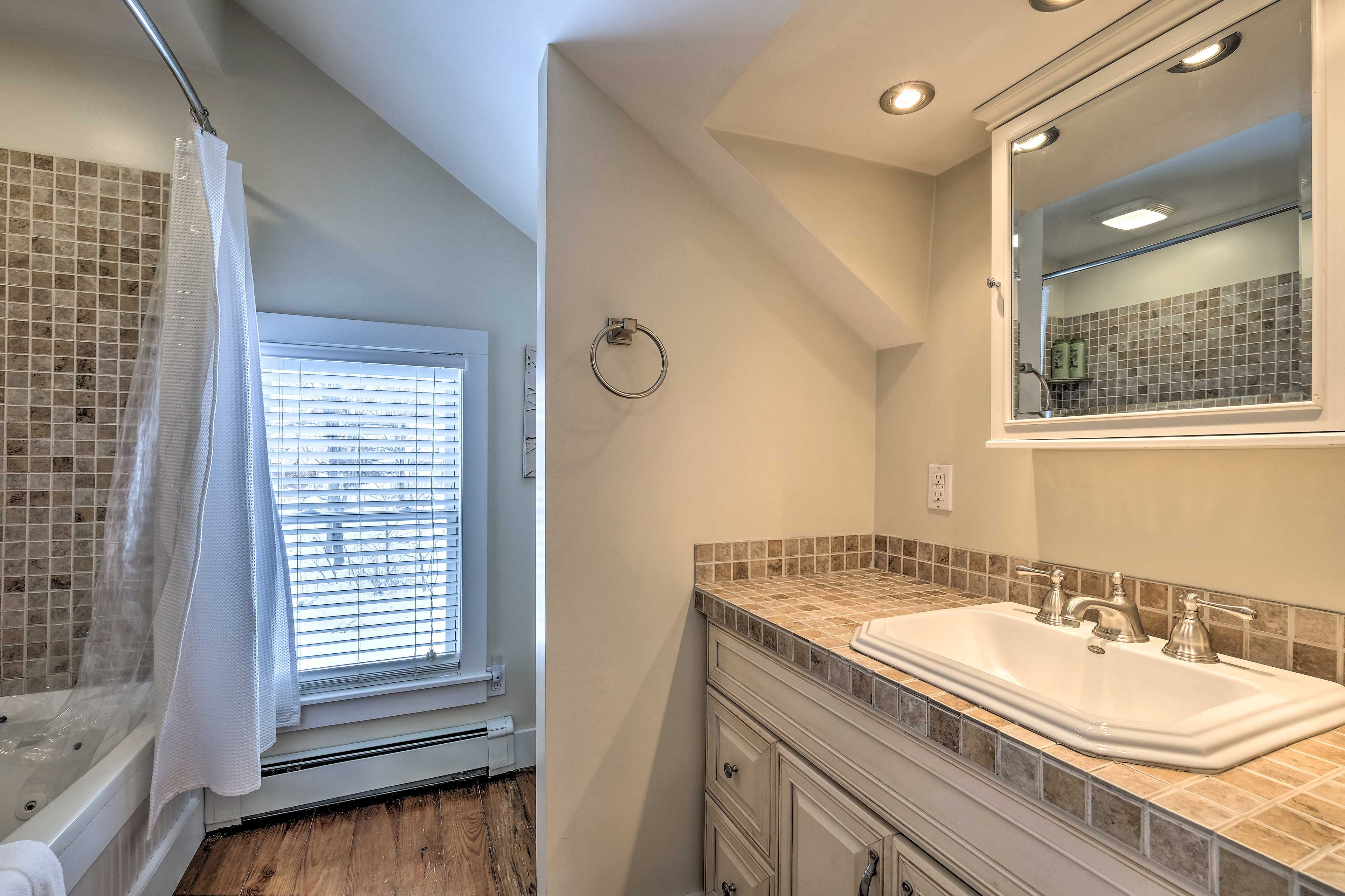The master bathroom includes a spacious vanity and shower/tub combo.