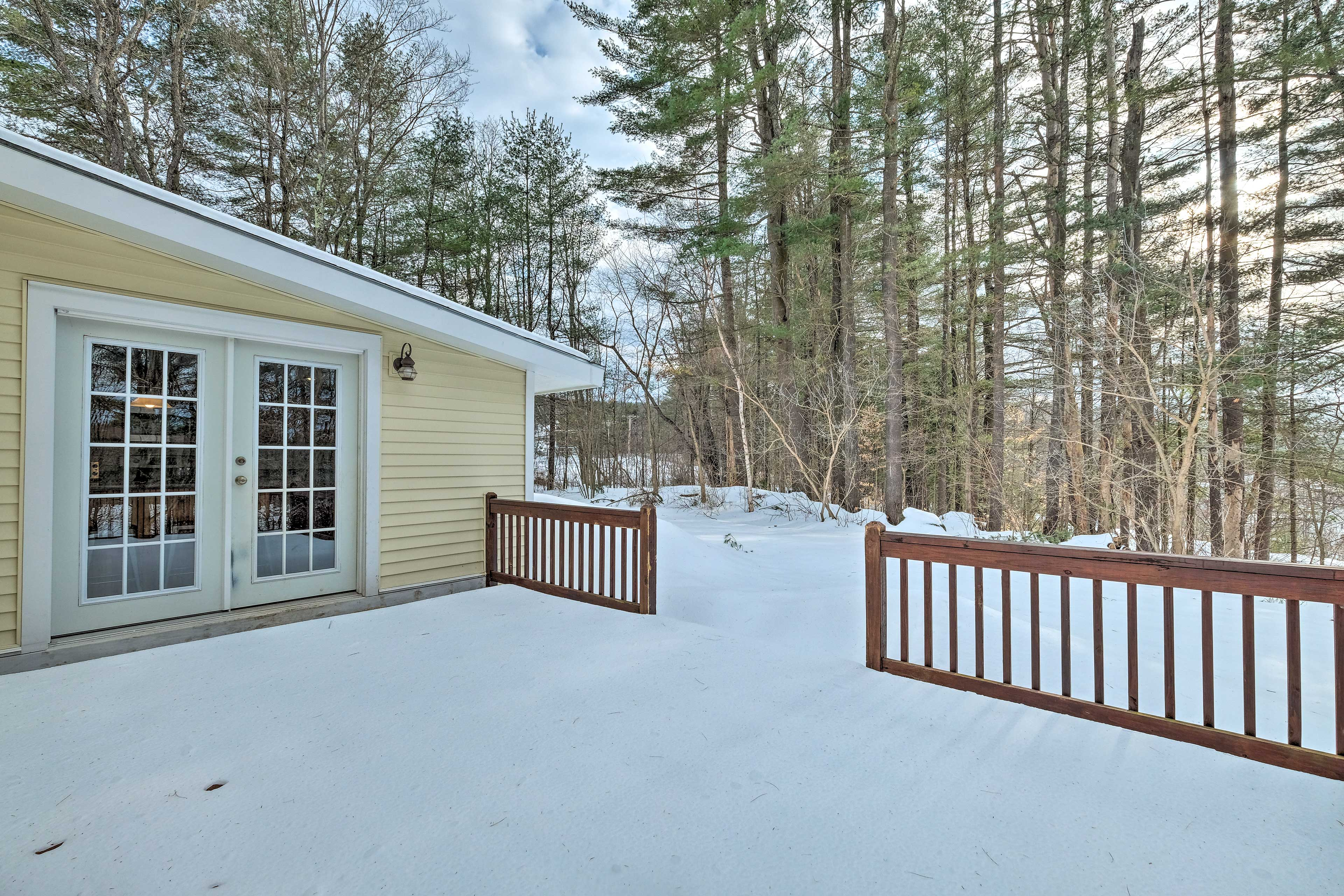 The spacious back deck offers great views of surrounding pine trees.