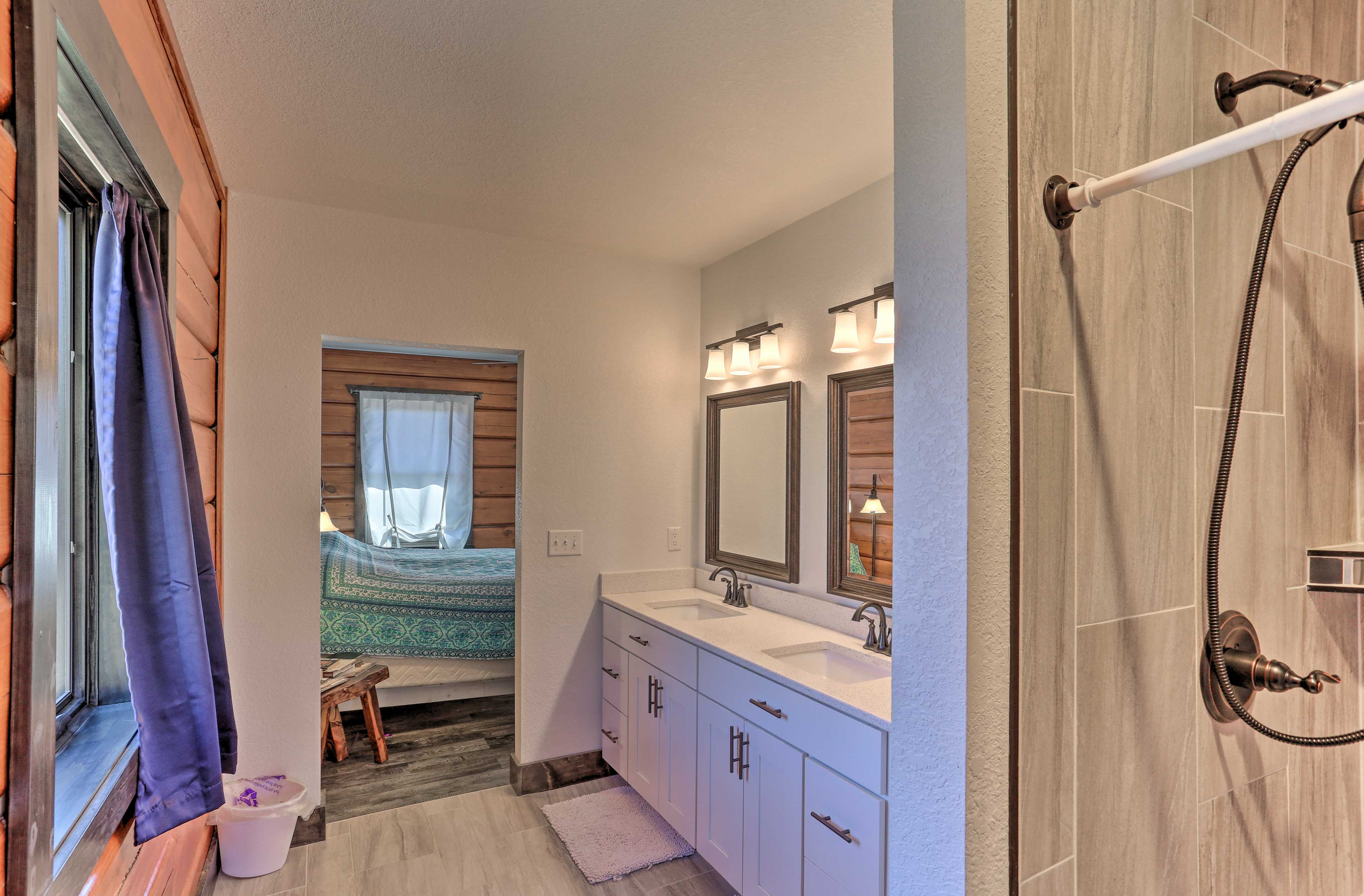 This full bathroom boasts double sinks and a shower.