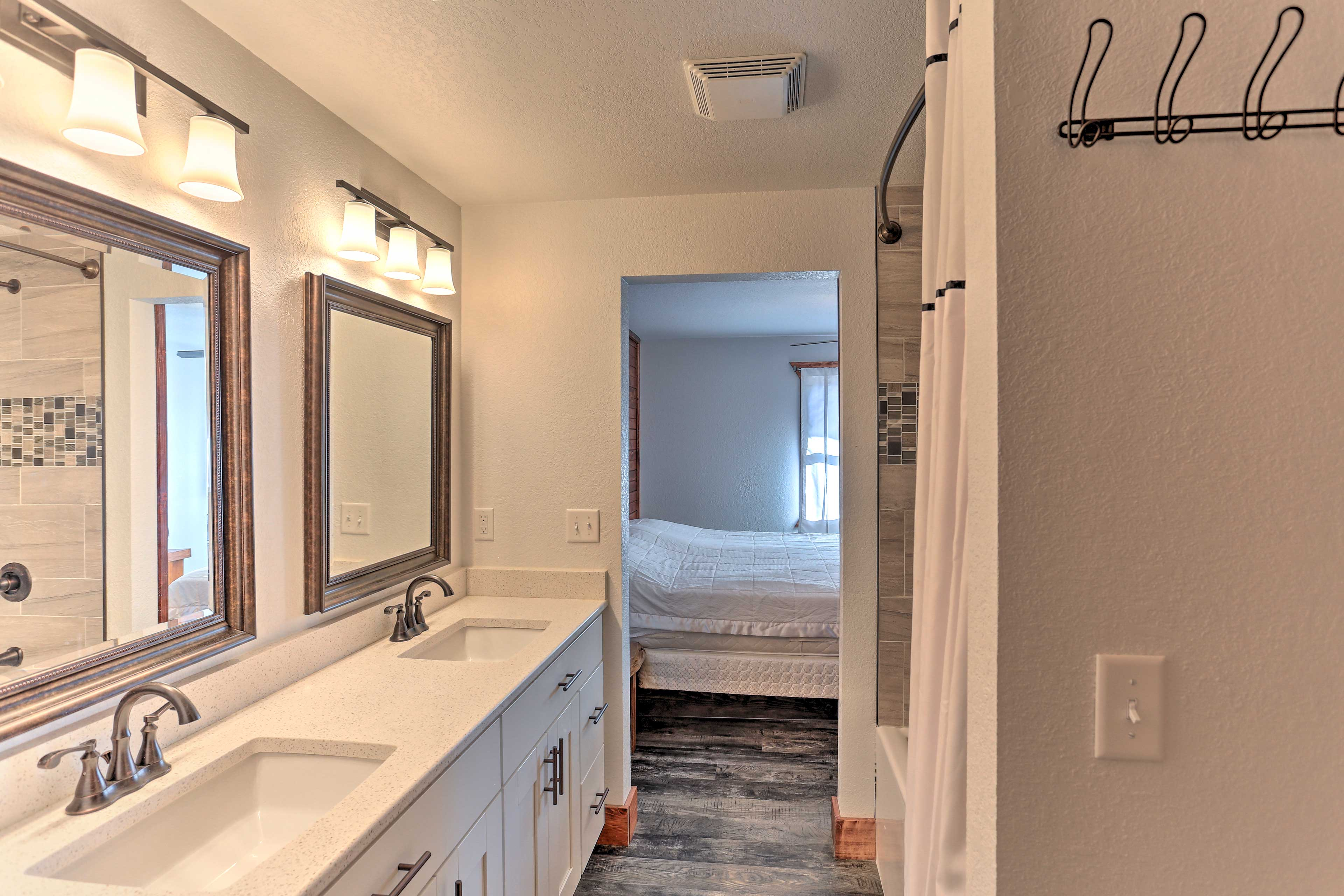 Upstairs, this sleek full bath hosts double sinks and a shower/tub combo.