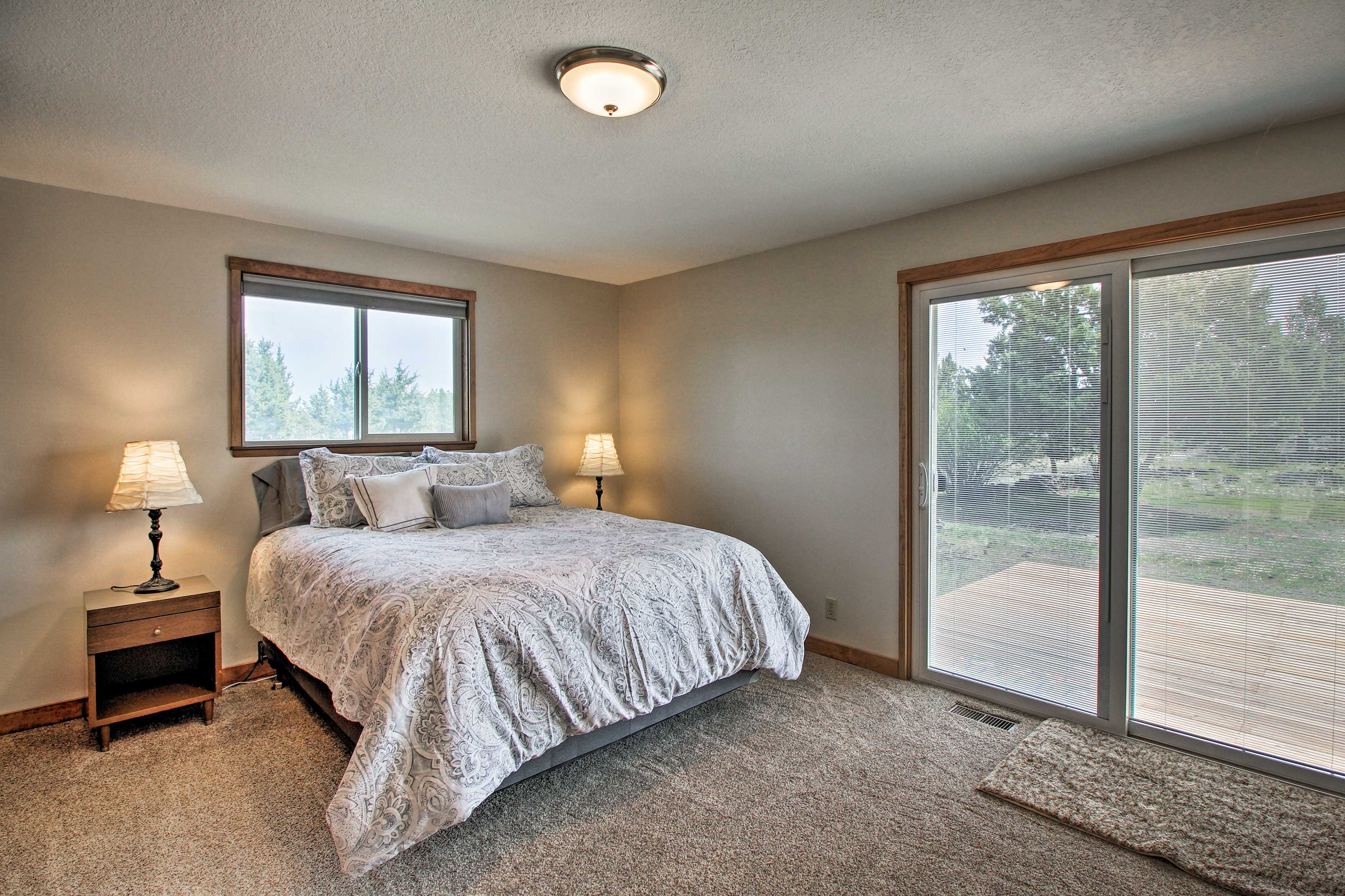 The first bedroom has access to one of the 2 decks and a queen-sized bed.