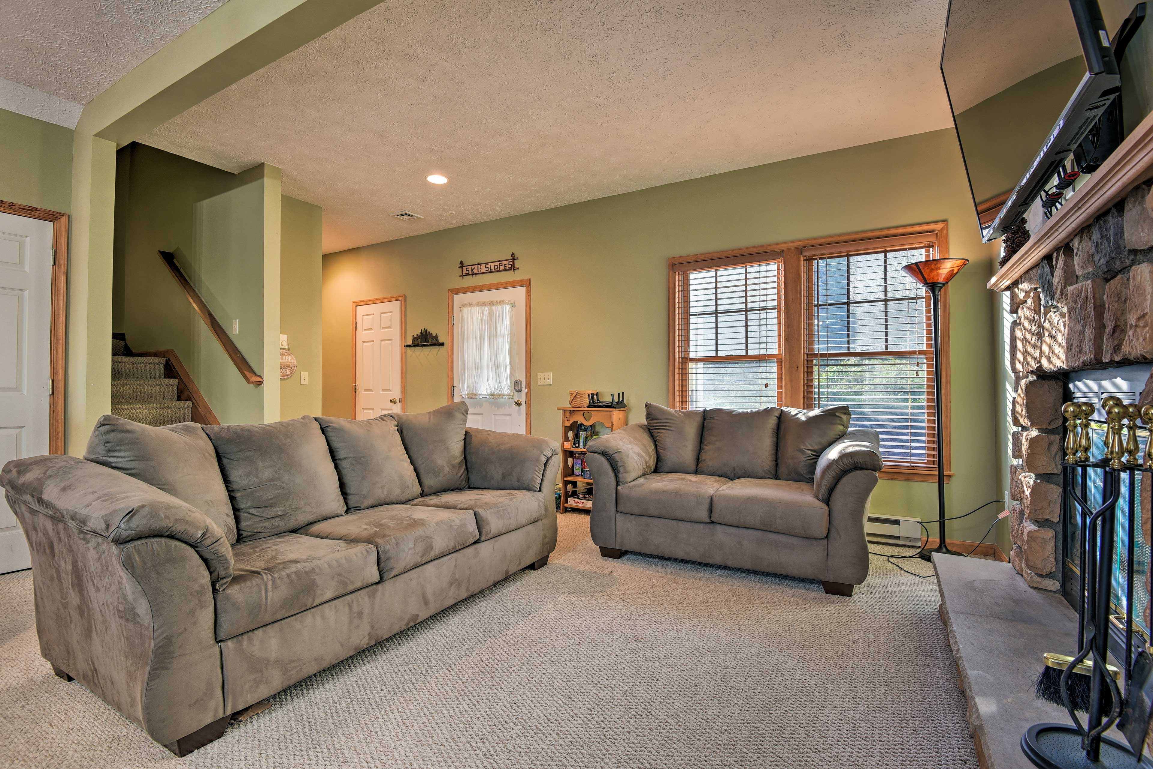 The living room is lined with windows and offers plenty of natural sunlight.