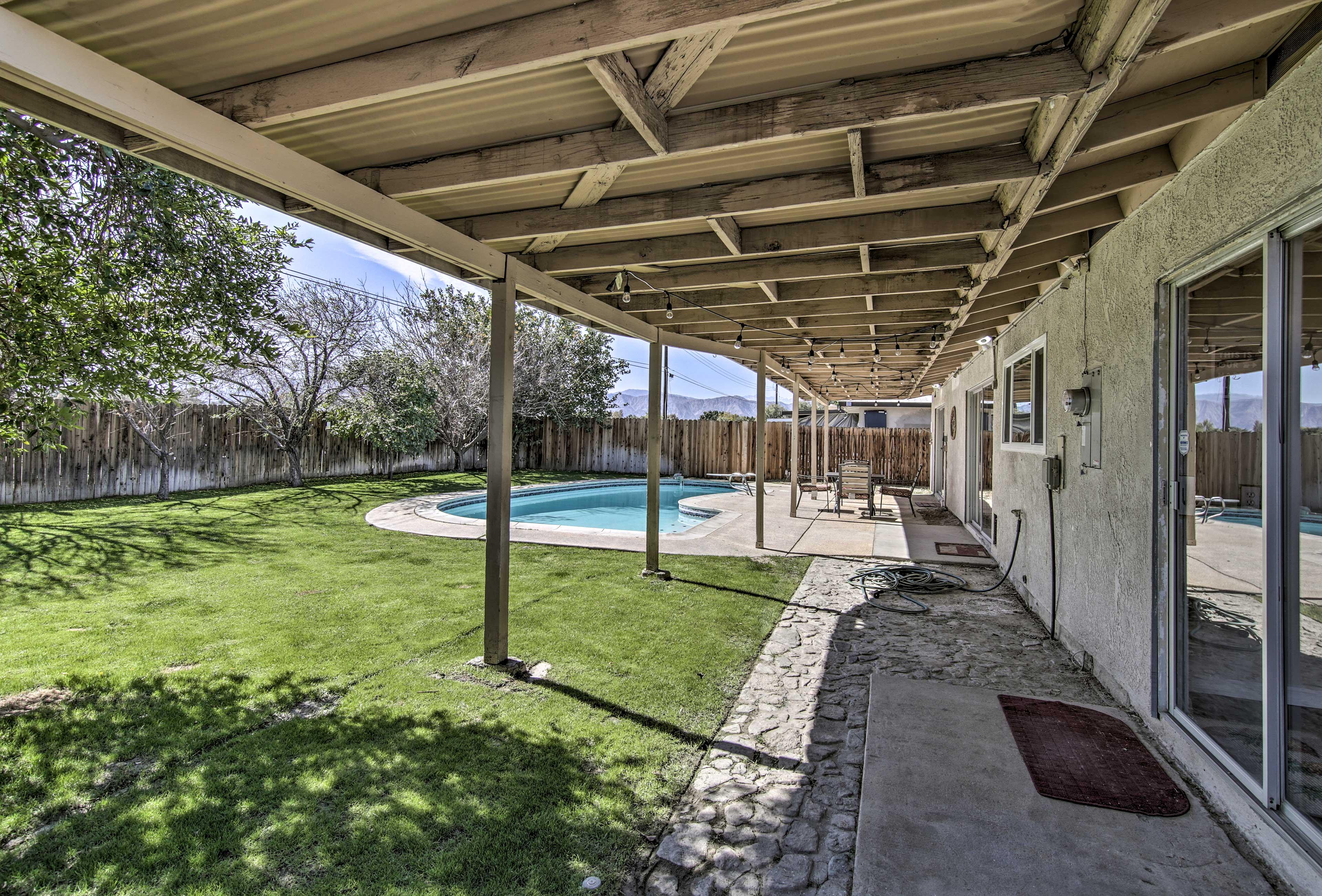 The backyard features artificial grass.