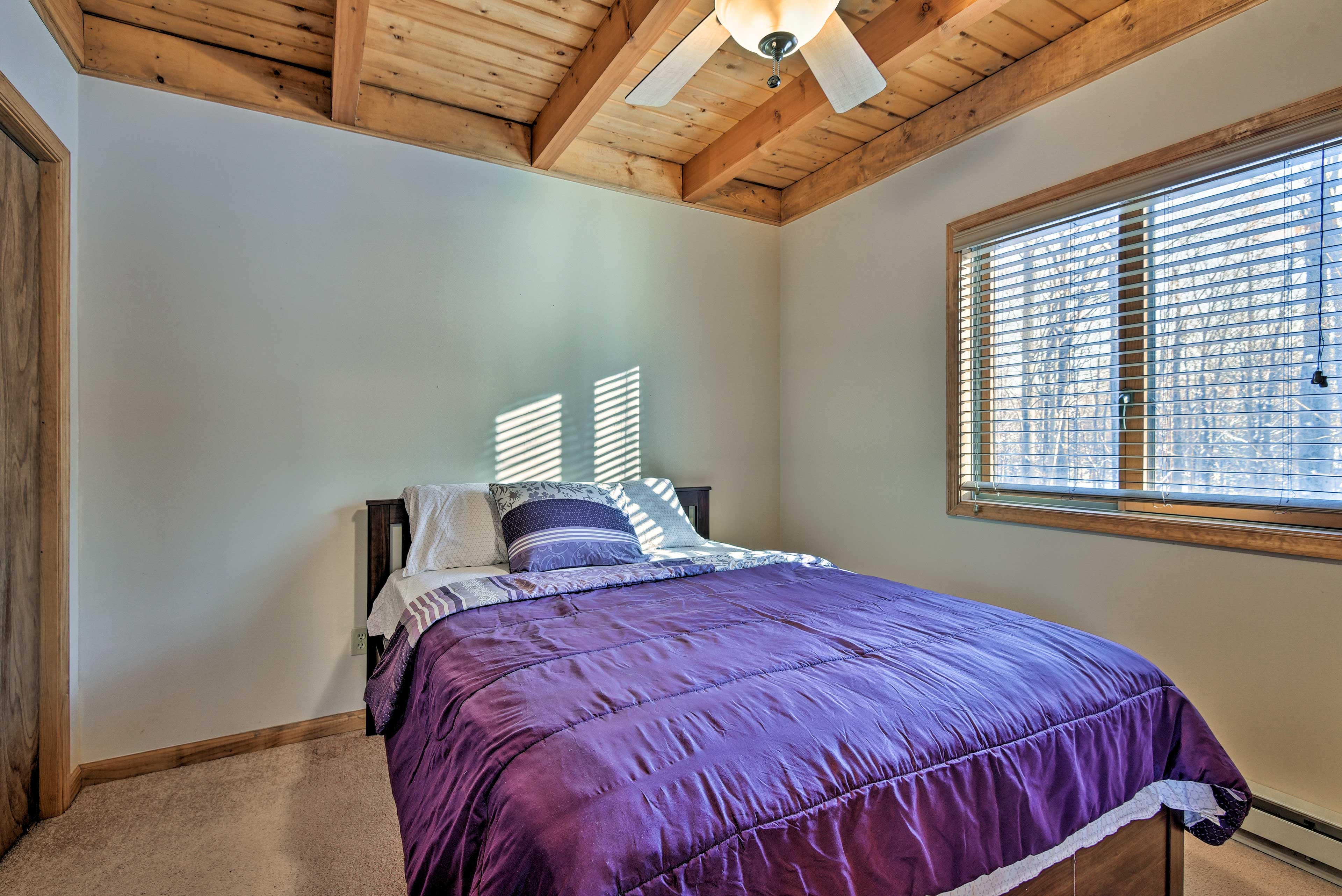 This third bedroom hosts a queen bed and rustic wood ceilings.