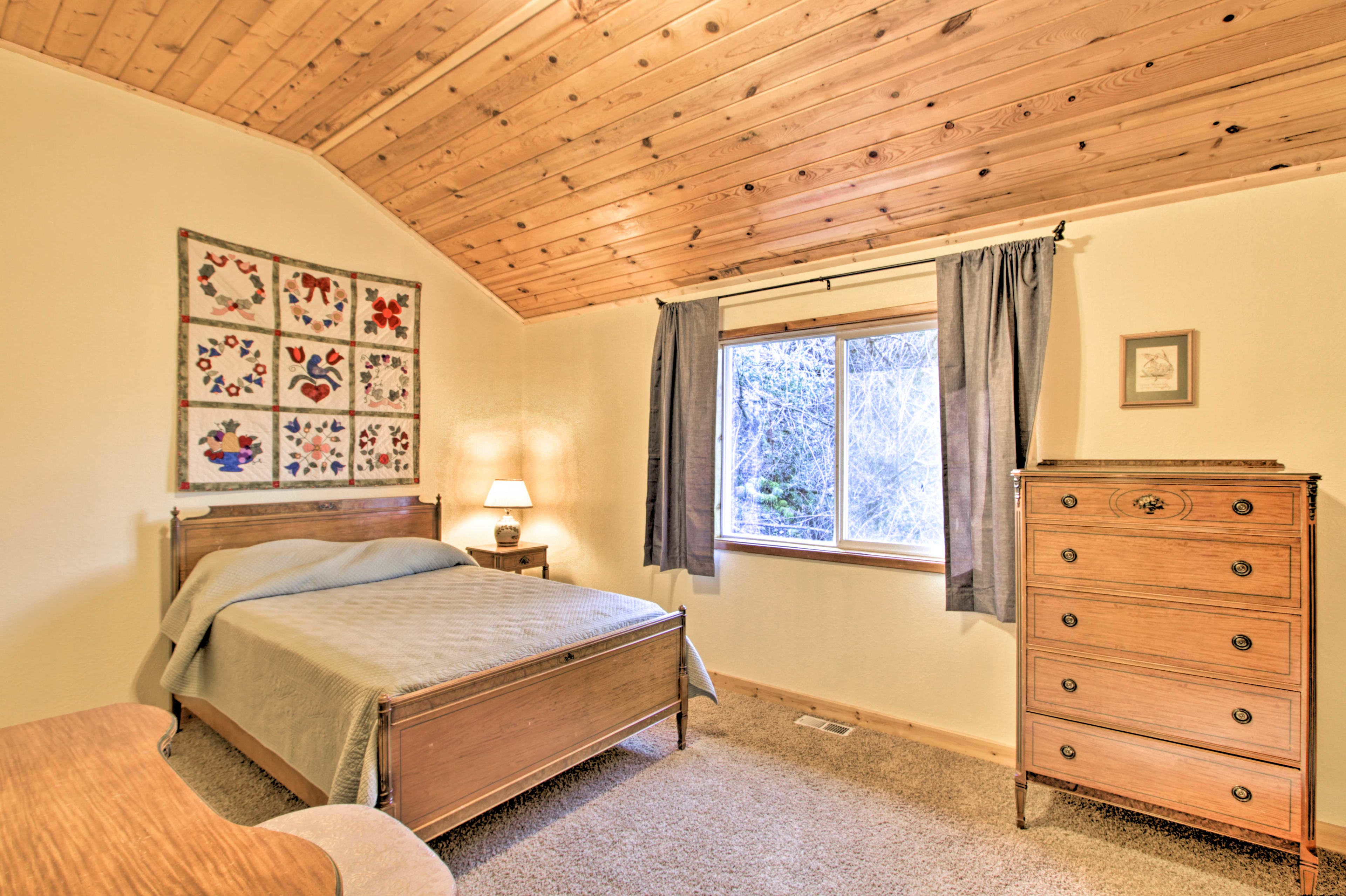 This second bedroom features a full bed and wood-paneled ceilings.