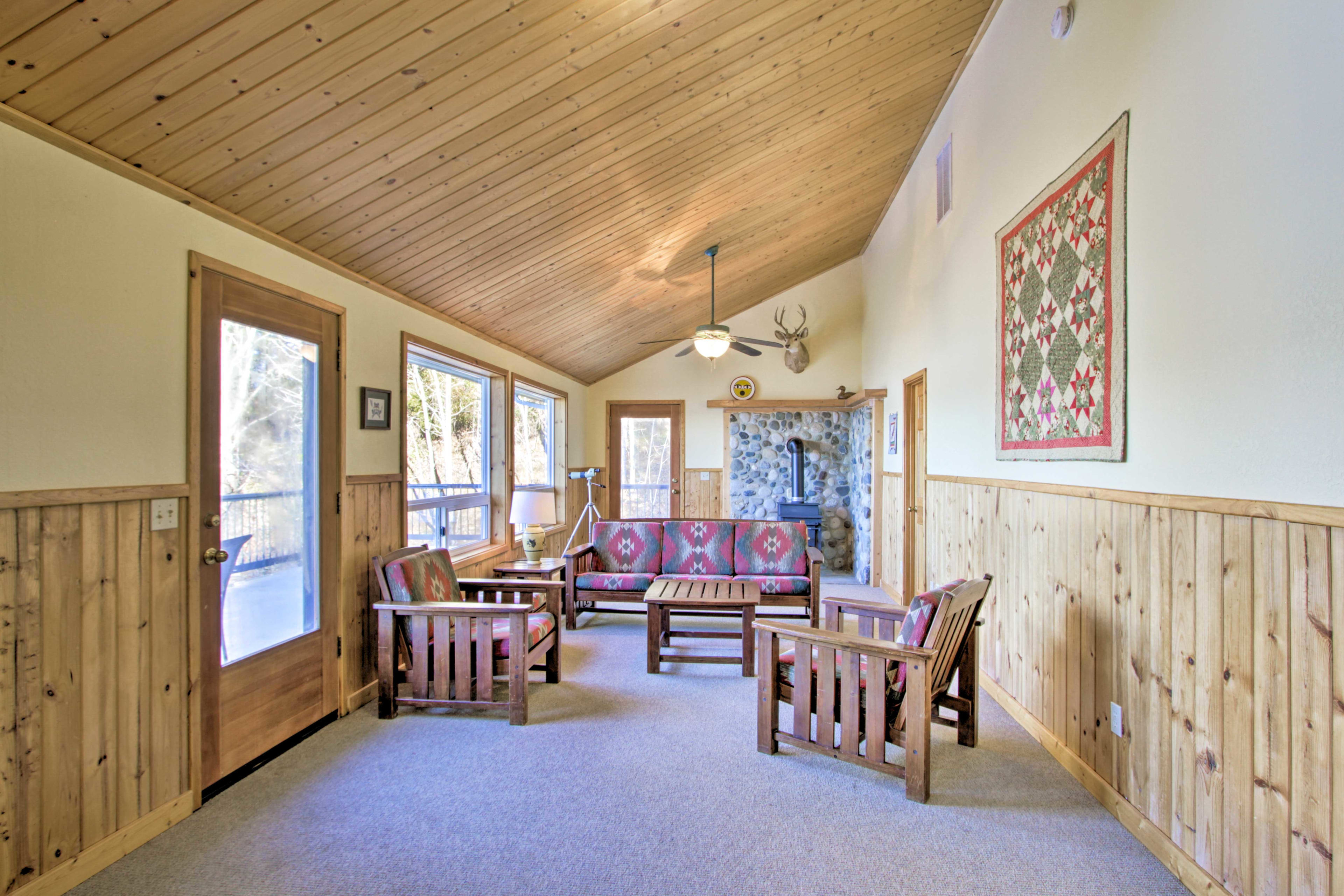 The upstairs seating area boasts a telescope, wood-burning stove & deck access.
