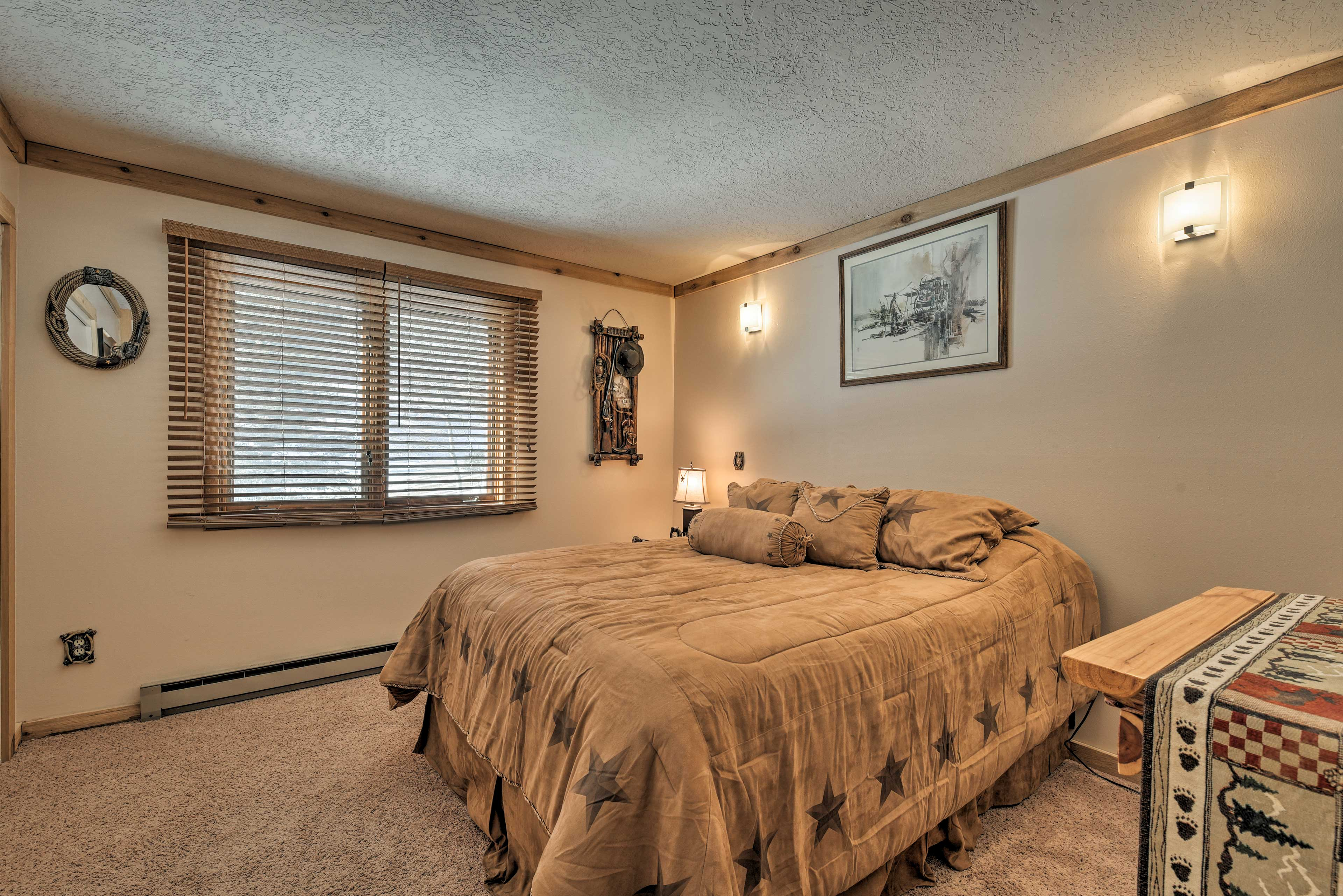 The master bedroom boasts a queen-sized bed and rustic decor.