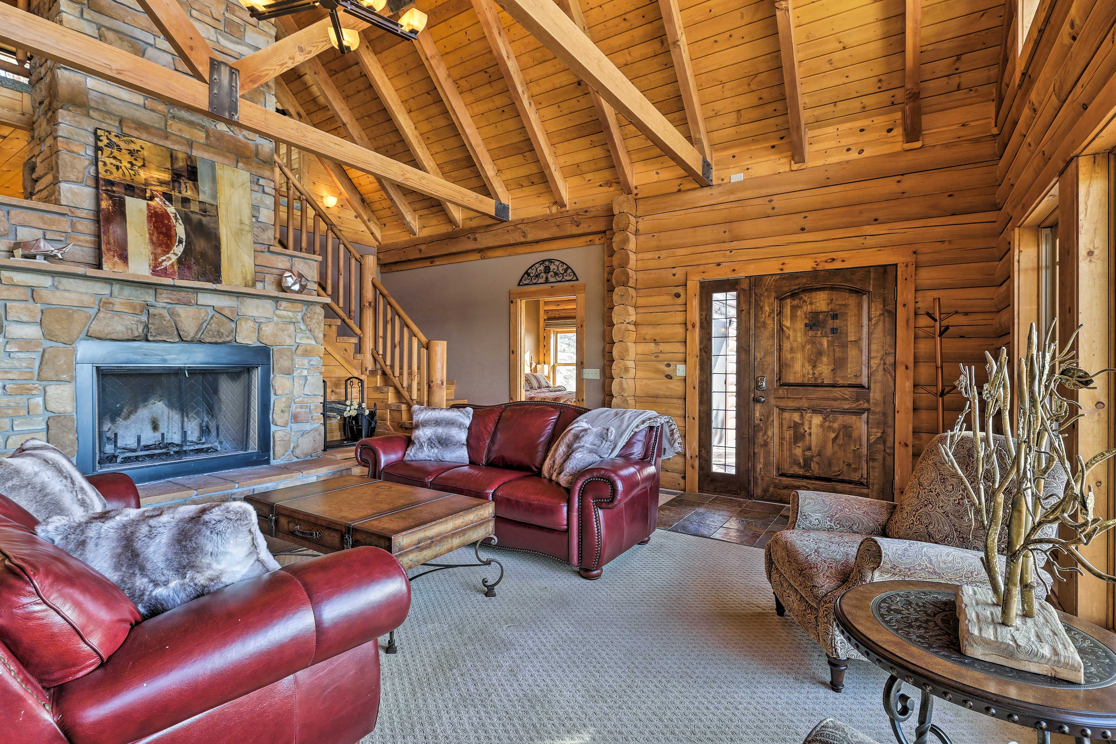 The stone fireplace and leather couches makes the living room cozy.